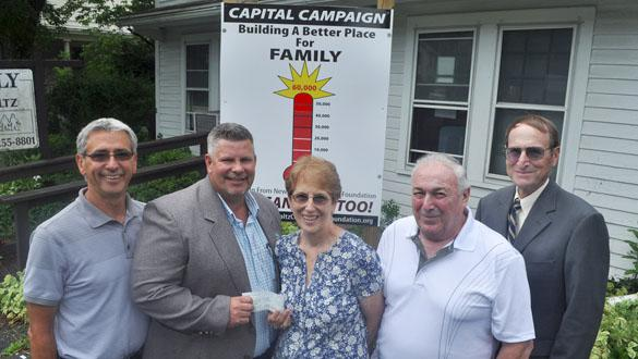NPCF board members present Family of New Paltz with a check for $xxxxx toward the renovation of their building.