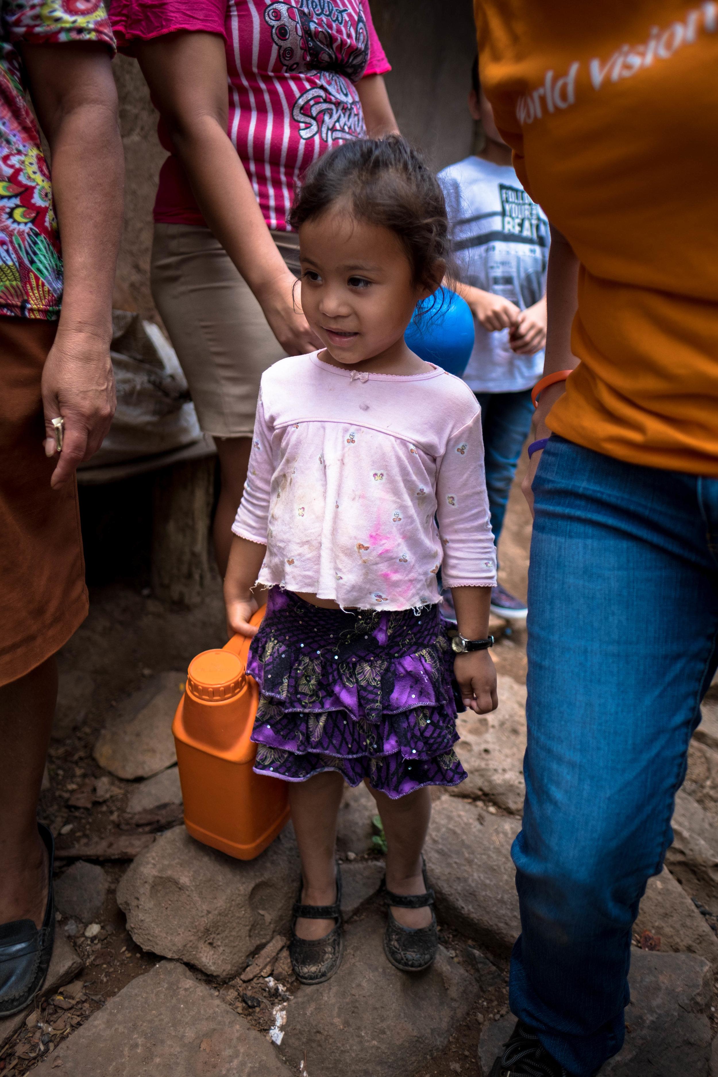 Honduras 18 day 2_little girl holds water container.jpg