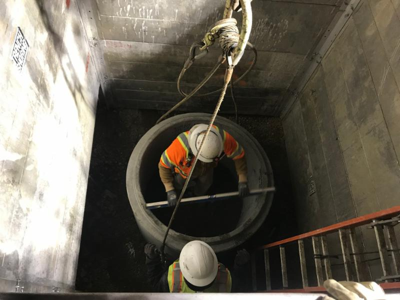 MCTC workers coordinate with Paradigm Mechanical to install a sump pit at the base of an elevator shaft.