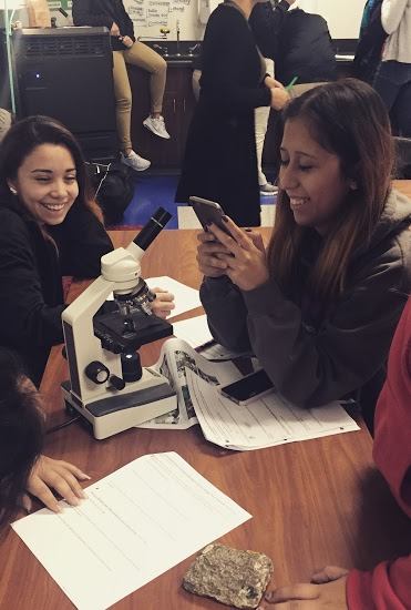The student in this picture isn't texting... She's instagramming a thin section photo!
