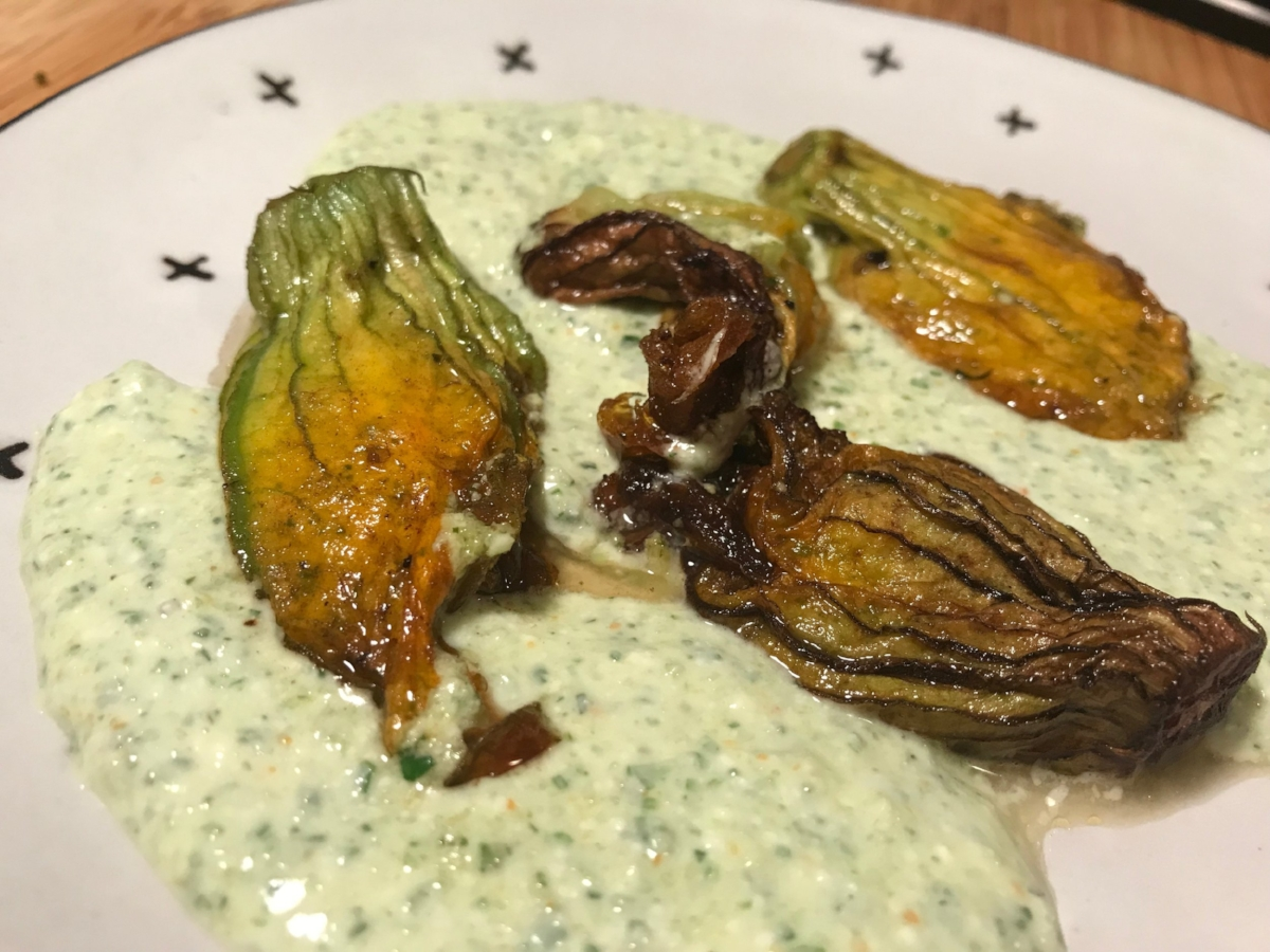 Fried  squash blossoms  with a filling and sauce made from blended feta, olive oil, and chopped  garlic scapes  and  spring onions.