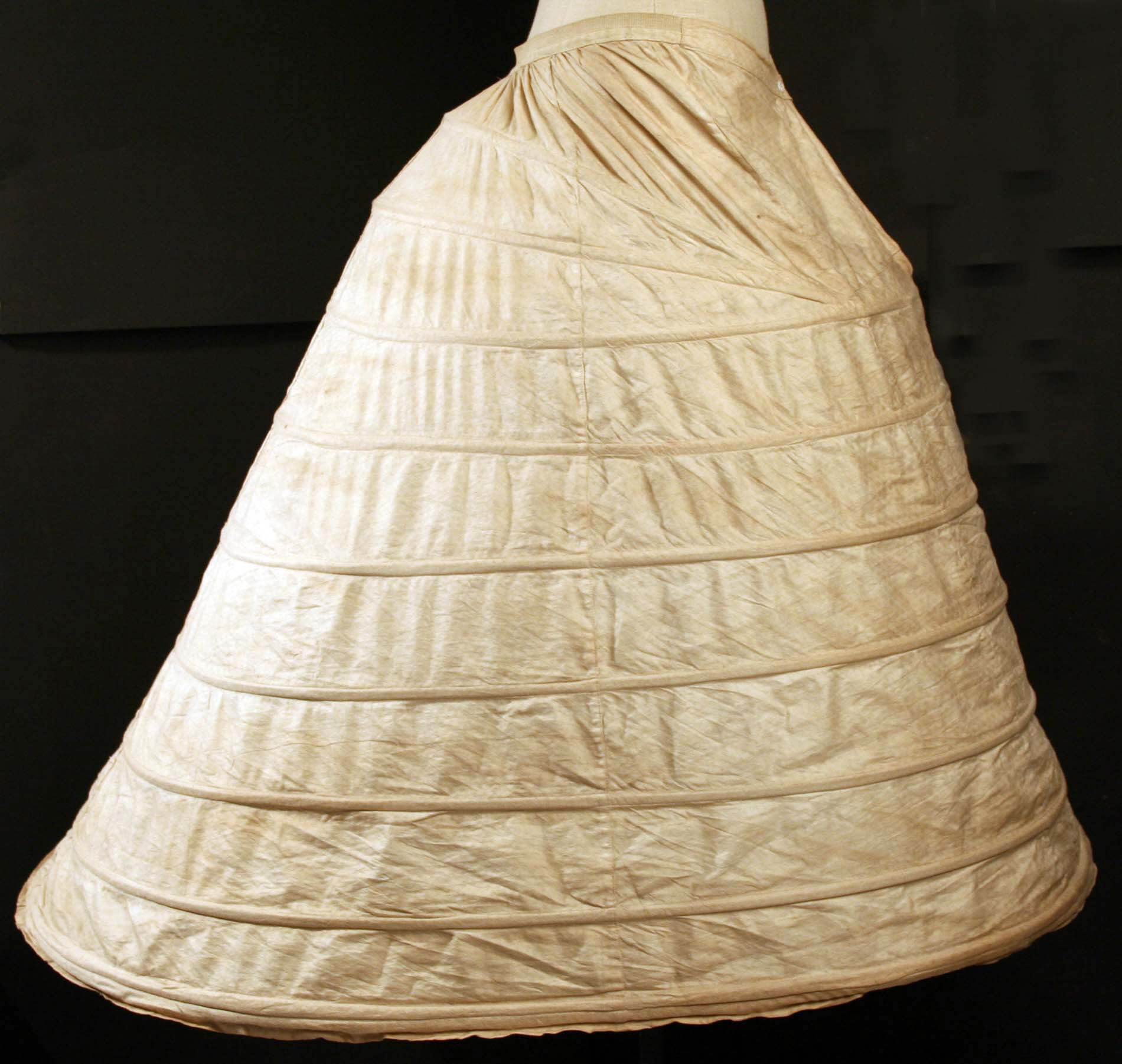 This 1862 crinoline model had fabric sewed on to help create a smooth, uninterrupted skirt line. Girls usually had to wear at least one under petticoat to make sure the bands of their cage didn't show through. Because, horrors! The more bands there were, the most expensive the crinoline tended to be.   Purchase, New York Historical Society (by exchange), 1985.