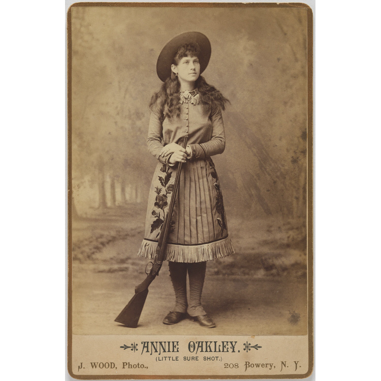 Annie Oakley took pains to looks young and innocent, which is part of what let audiences enjoy the terrifying spectacle of watching a lady hit targets with terrifying accuracy.   National Portrait Gallery, Smithsonian Institution