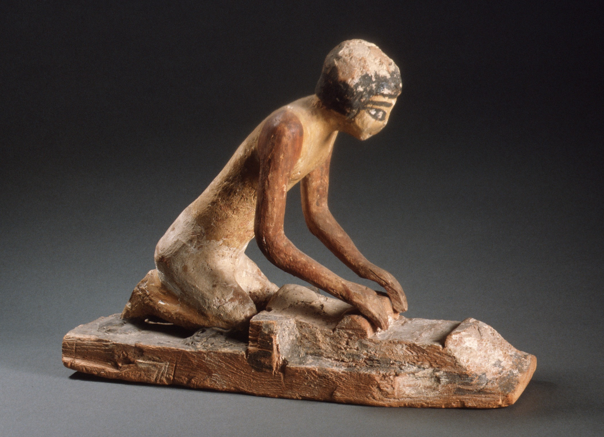 Model of a woman grinding grain, which she'll use both to make bread and to brew beer. - From Egypt, First Intermediate Period/early Middle Kingdom, 2134-1991 BCE. Courtesy of Los Angeles County Museum.