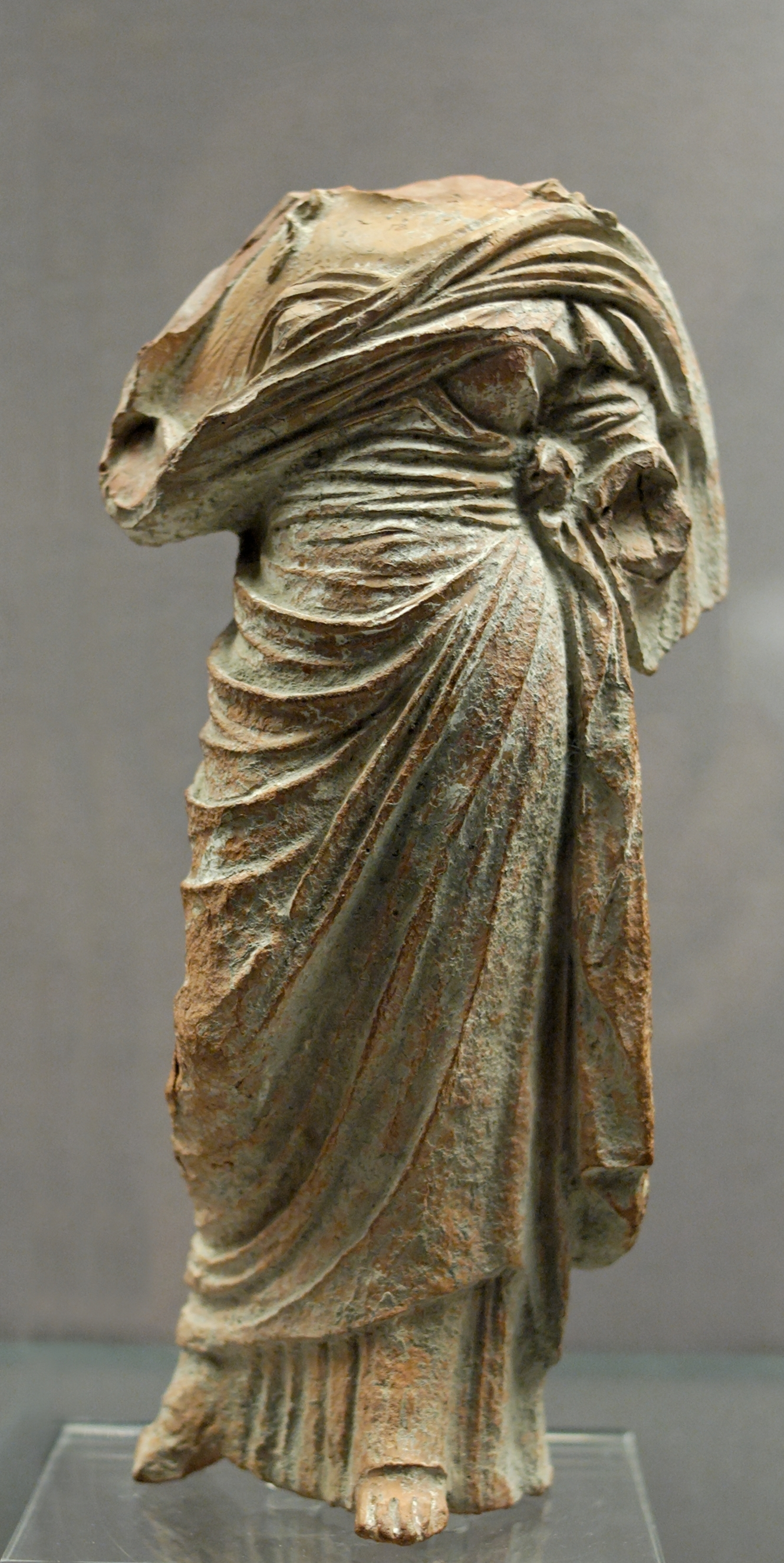 Rocking a chiton, a himation, and no head, as seems to be par for the course with lady art of ancient Greece.   Wikicommons