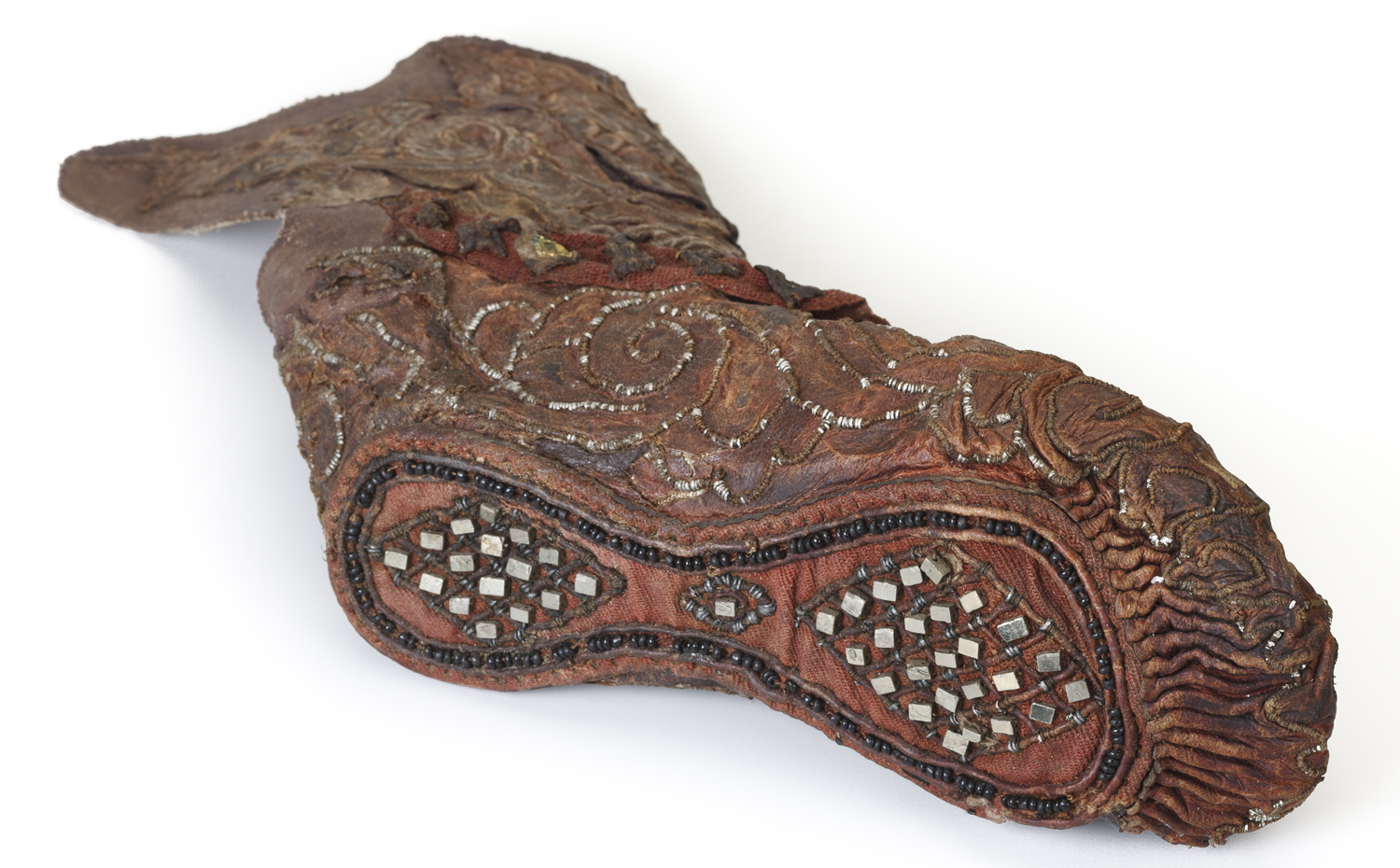 This woman's shoe includes leather, tin, pyrite crystals, gold foil, and glass beads.