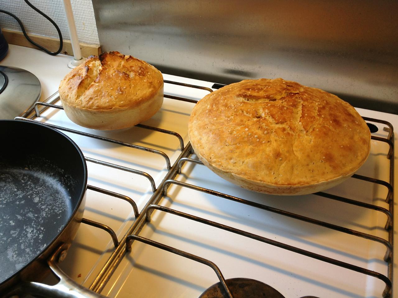 Scanpan overlevede  Scanpans website var ikke meget for at komme med entydigede anvisninger angående deres produkters gangbarhed i en varm (250+ grader) ovn i længere tid. Men de skrev dog at den ku' tåle en tur i ovnen ved 260 grader, så jeg gav det et skud, og den (altså min Scanpan) overlevede. Det gjorde dejen imidlertid ikke. Den bleve helt brun og hævet :). Så nu er det ikke længere kun min lille stengryde (se brødet til venstre) der kan levere Jim Lahey-brød - det kan den noget større Scanpan også, hvilket kan være praktisk en dag som i dag hvor jeg skal spise med 14-15 andre mennesker.