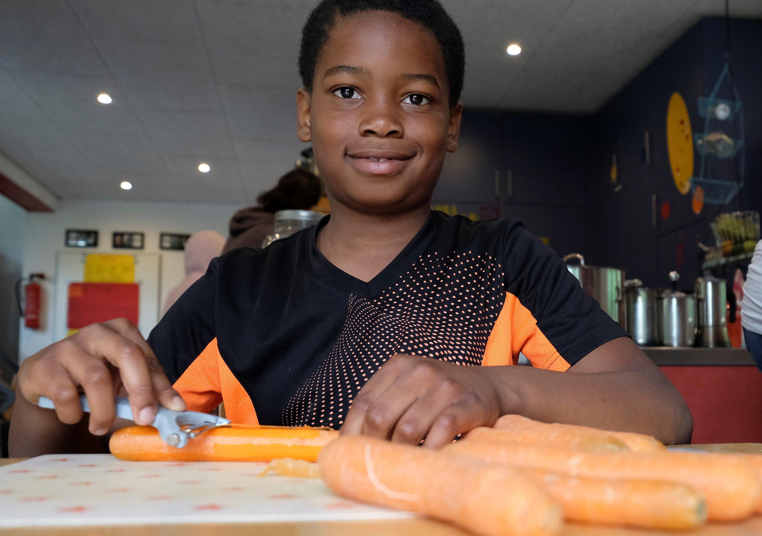 Bild aus dem Programm CHILDREN Entdecker (Kinderarmut): Junge schneidet Karotten
