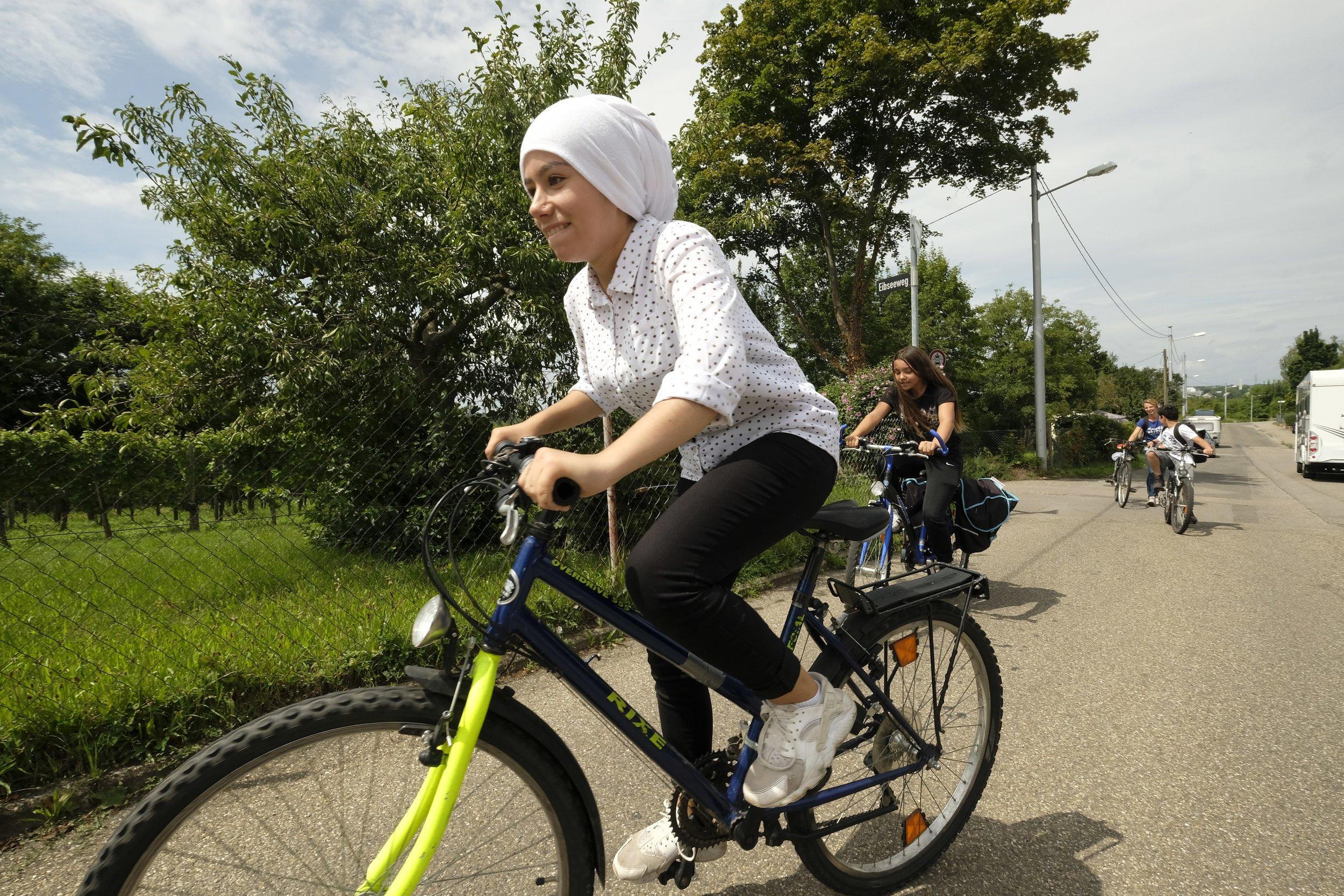 Bild aus dem Programm CHILDREN Entdecker (Kinderarmut): Mädchen mit Kopftuch beim Fahrradfahren