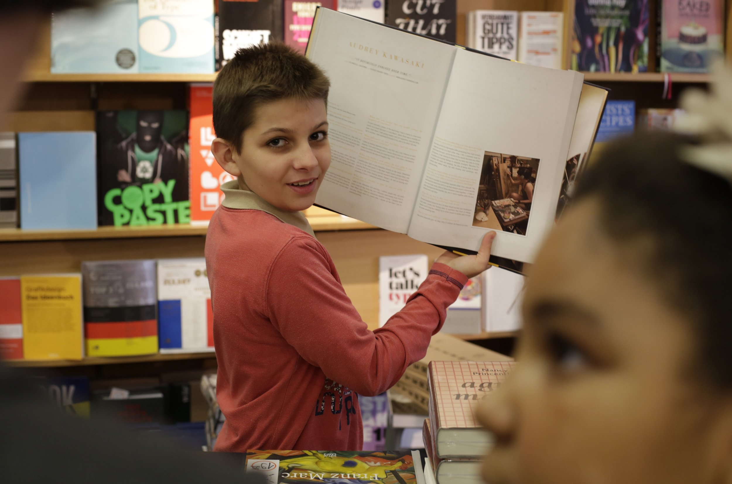 Bild aus dem Programm CHILDREN Entdecker (Kinderarmut): Junge steht vor einem Bücherregal und hält ein Buch in den Händen
