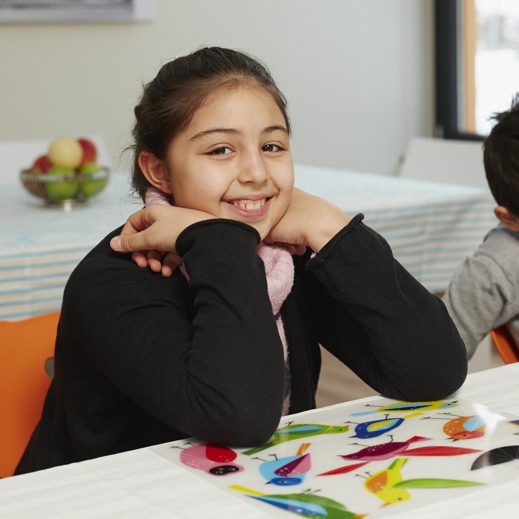 Ein durch den CHILDREN Mittagstisch gefördertes Mädchen sitzt lächelnd an einem gedeckten Tisch.