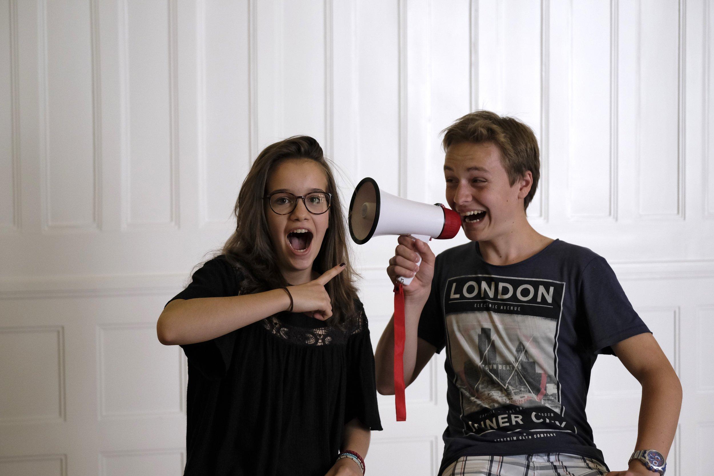 Bild vom CHILDREN Kinderbeirat (Partizipation): Ein Junge hat ein Megafon in der Hand, ein Mädchen zeigt auf ihn