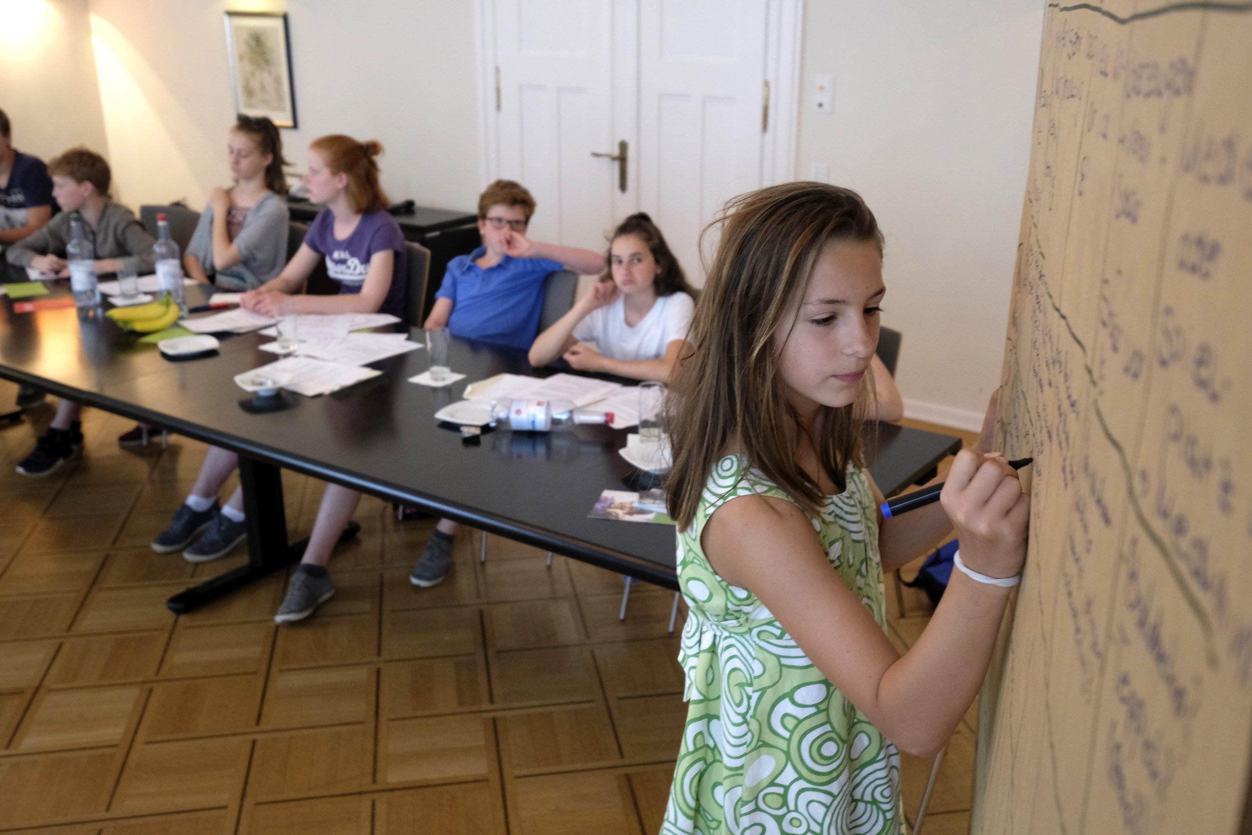 Bild vom CHILDREN Kinderbeirat (Partizipation): Ein Mädchen macht Notizen auf einer Stellwand