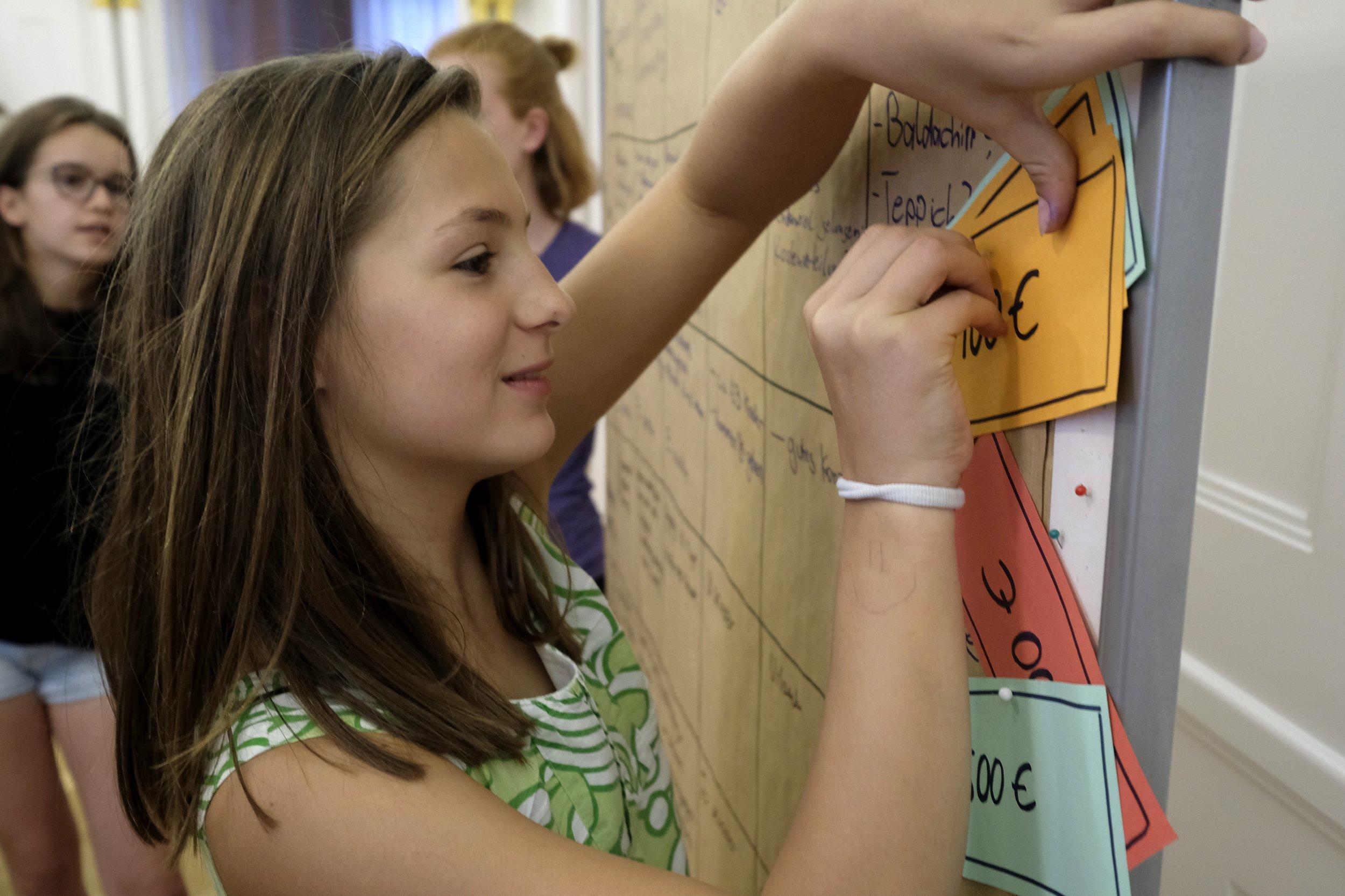 Bild vom CHILDREN Kinderbeirat (Partizipation): Ein Mädchen pinnt gebastelte Geldscheine an eine Stellwand