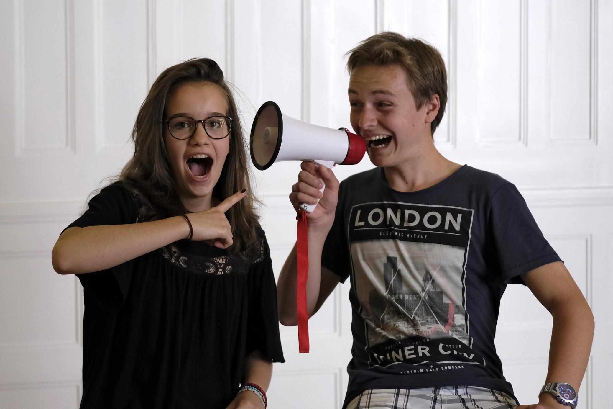Zwei Jugendliche mit einem Megafon.