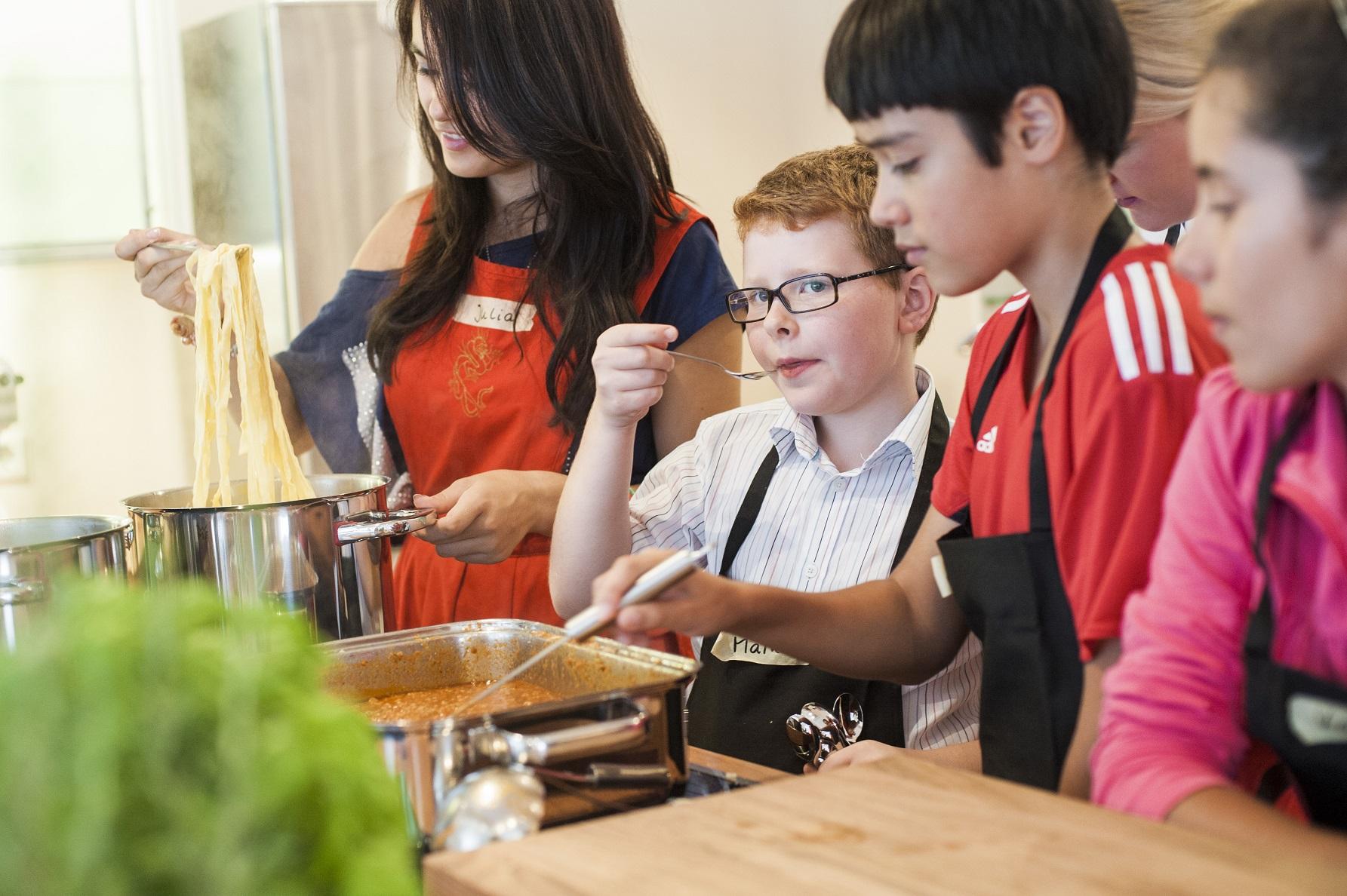 Eine Gruppe Kinder, die mit dem Programm CHILDREN Entdecker gefördert wird, kocht im Rahmen des CHILDREN Mittagstischs Pasta.