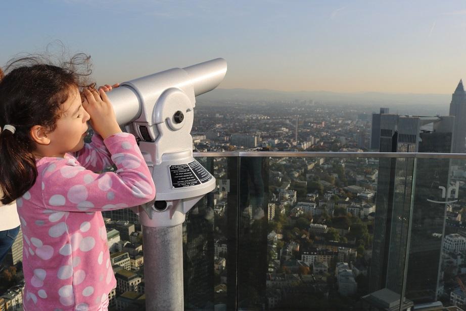 Mädchen auf einem Aussichtspunkt blickt mit einem Fernglas über die Dächer einer Stadt.