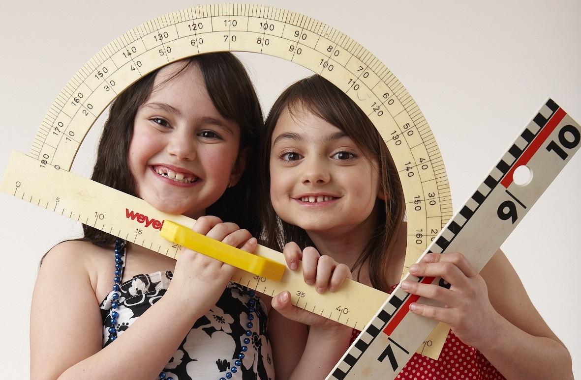Transparenz und Wirkung sind wichtig! Zwei lachende Mädchen halten Lineale vor ihre Gesichter.