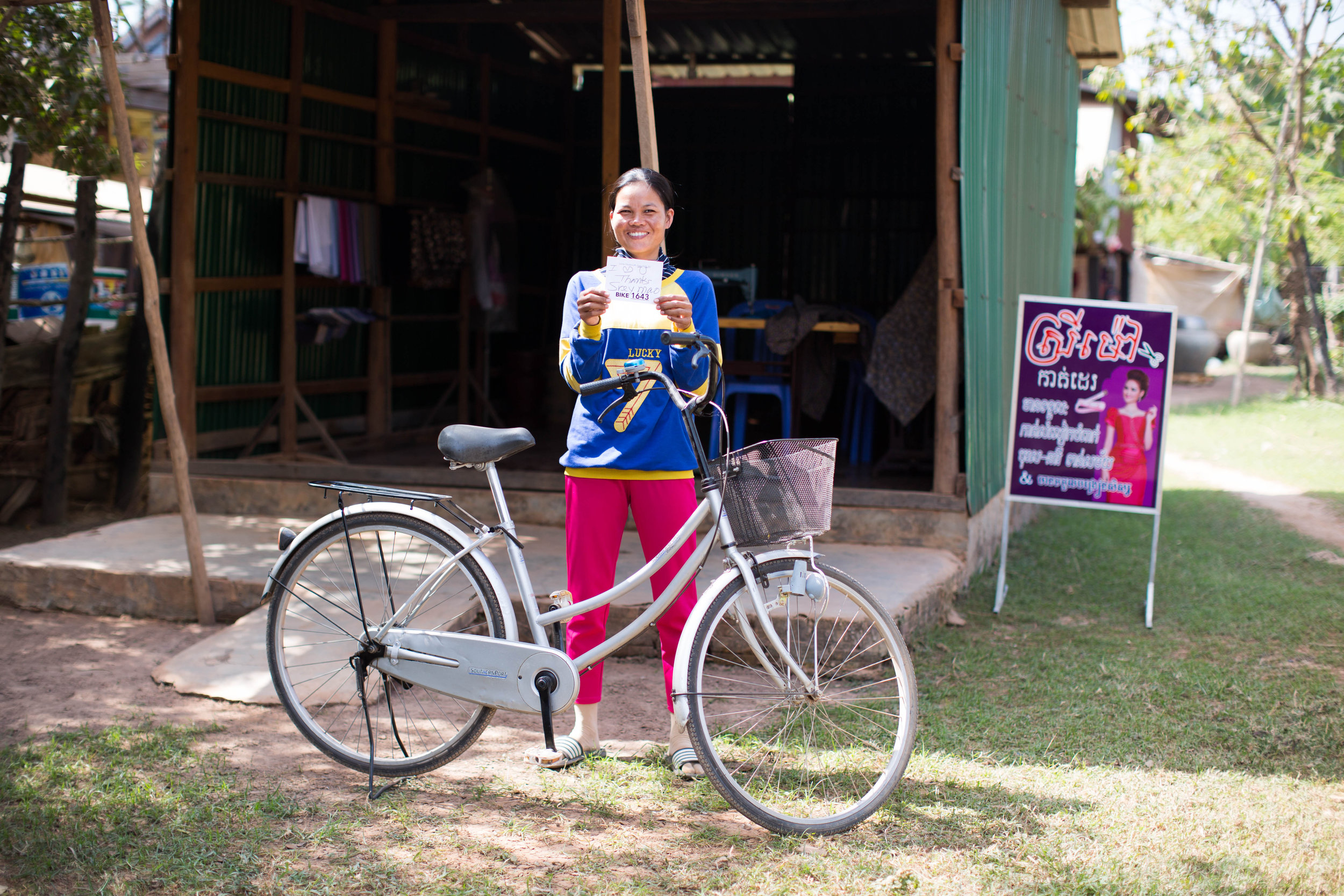 Sreymom, standing with her new bike, used a Tailwind Grant to help grow her sewing shop.