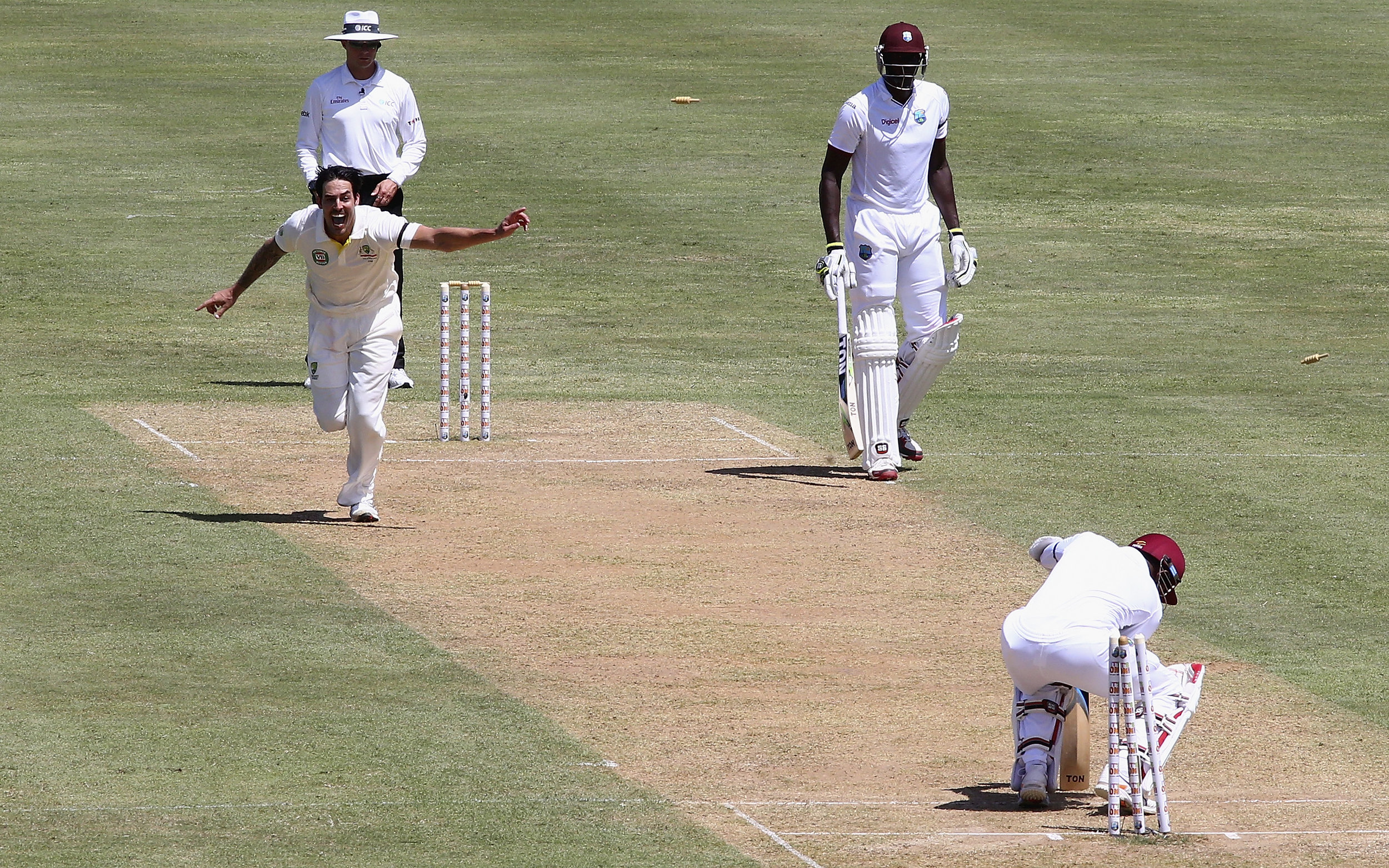 Mitchell Johnson celebrates after bowling Denesh Ramdin of West Indies