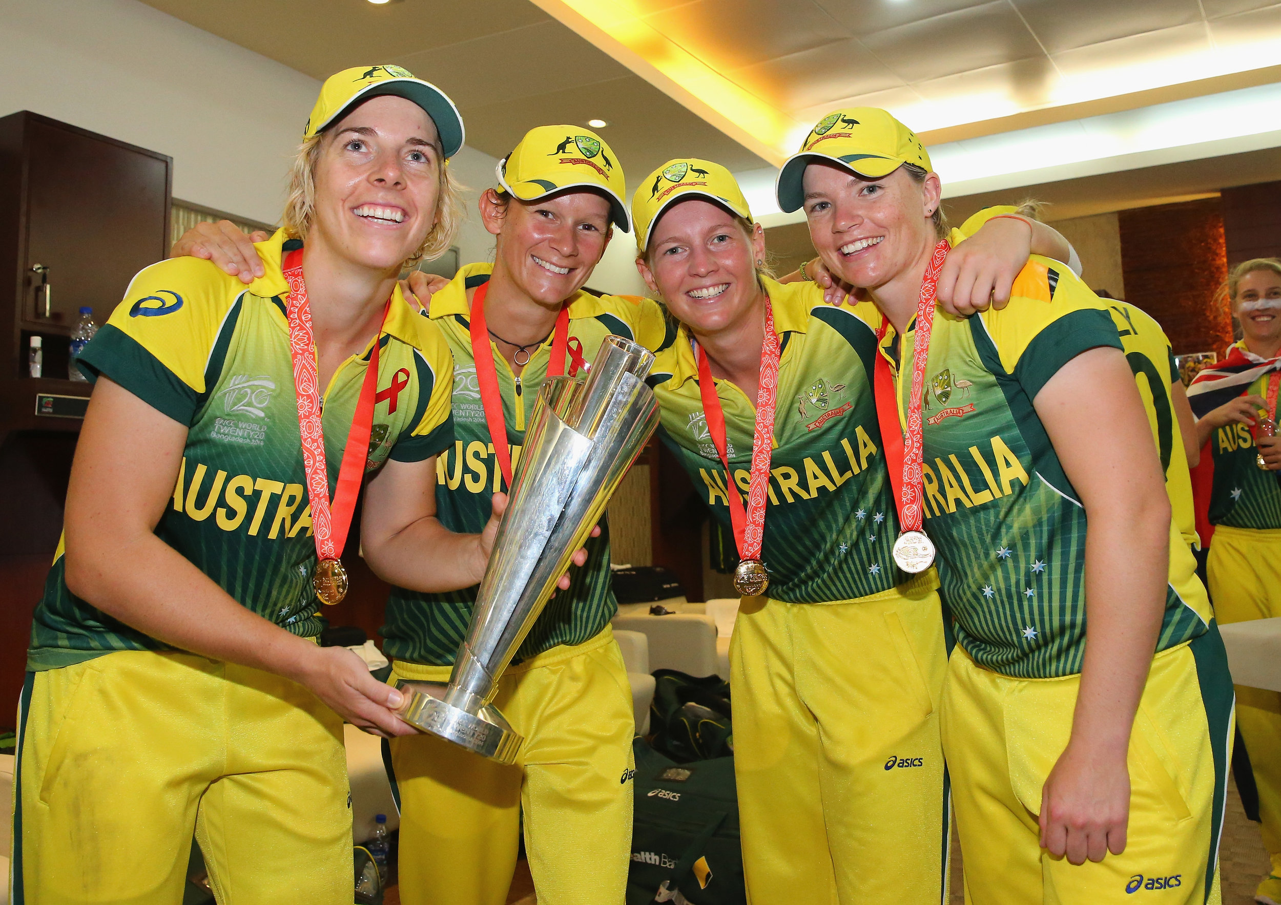 Elyse Villani, Julie Hunter, Meg Lanning and Jess Cameron pose with the trophy in the changing rooms after winning the the ICC Women's World Twenty20 final against England in 2014