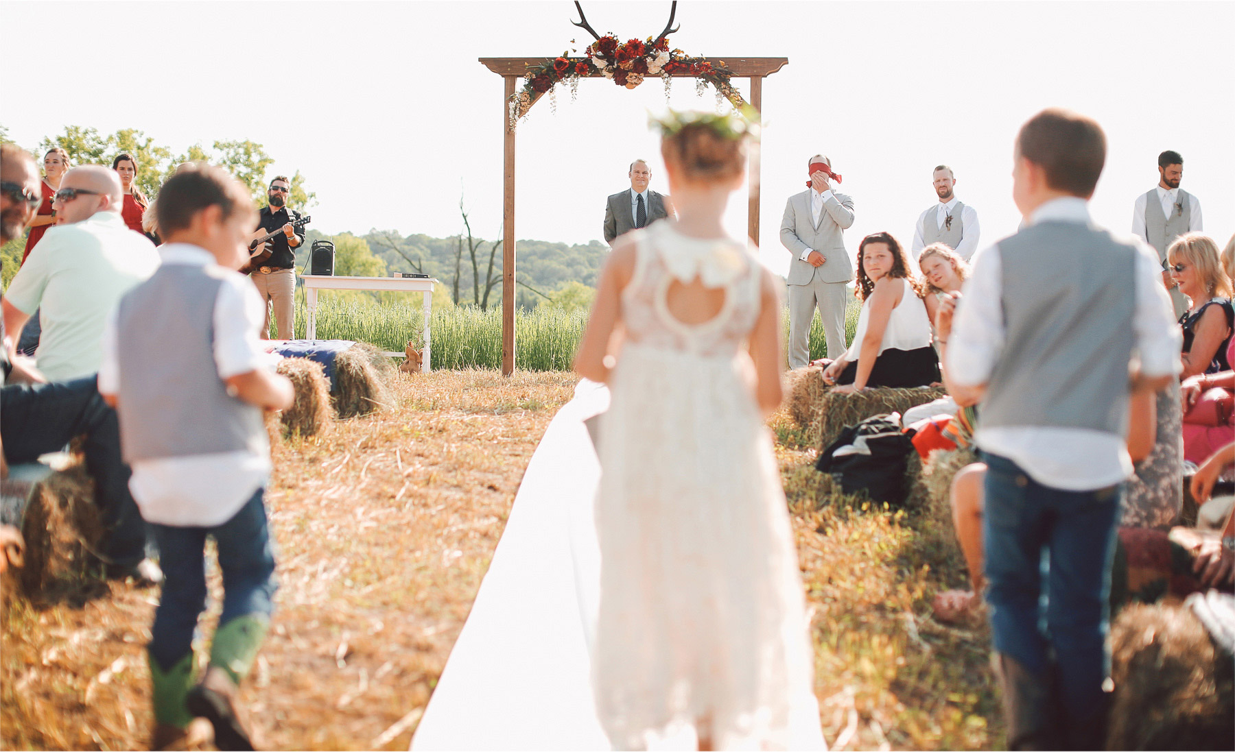 15-South-Haven-Minnesota-Wedding-Photographer-by-Andrew-Vick-Photography-Summer-Tomala-Farm-Ceremony-Groom-Blidefold-Flower-Girl-Ring-Bearer-Aisle-Hay-Bale-Vintage-Renee-and-Bobb.jpg
