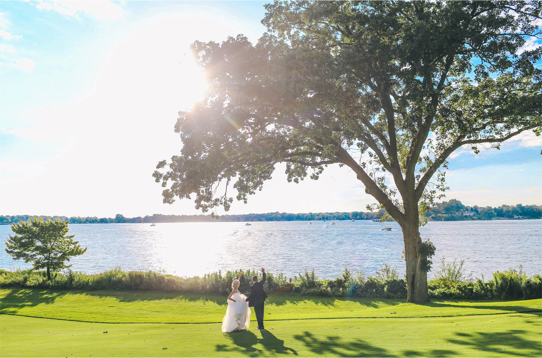 17-Minnetonka-Beach-Minnesota-Wedding-Photographer-by-Andrew-Vick-Photography-Summer-Lake-Lafayette-Club-Bride-Groom-Waving-Golf-Course-Emily-and-Jay.jpg