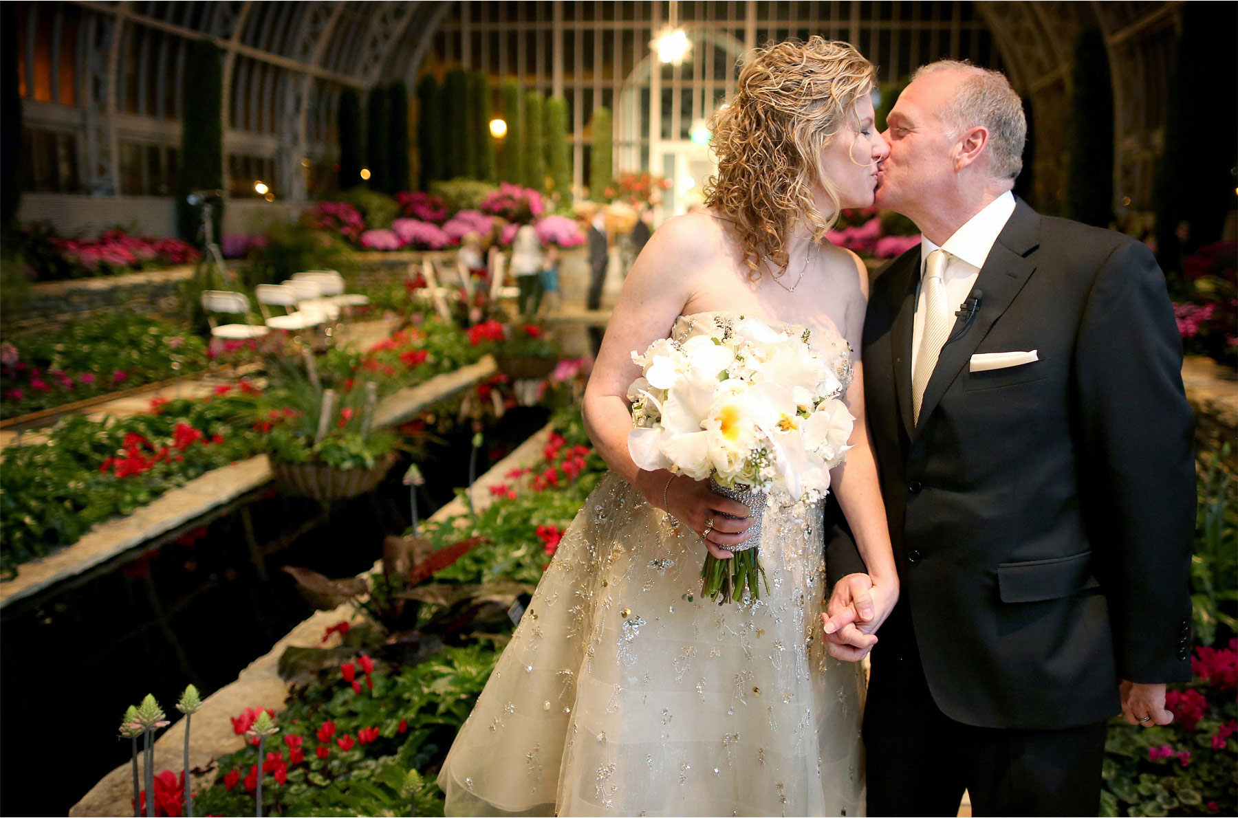 19-Saint-Paul-Minnesota-Wedding-Photographer-by-Andrew-Vick-Photography-Winter-Como-Park-Conservatory-Sunken-Garden-Bride-Groom-Kiss-Flowers-Night-Dannette-and-Darren.jpg