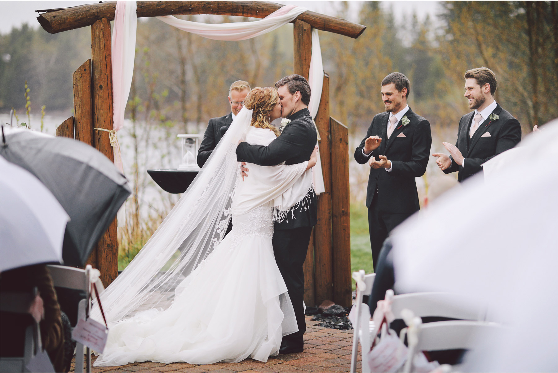 17-Minnesota-Wedding-by-Andrew-Vick-Photography-Grand-Superior-Lodge-Duluth-Two-Harbors-Outdoor-Ceremony-Kiss-Rain-Umbrellas-Veronica-and-Tyler.jpg