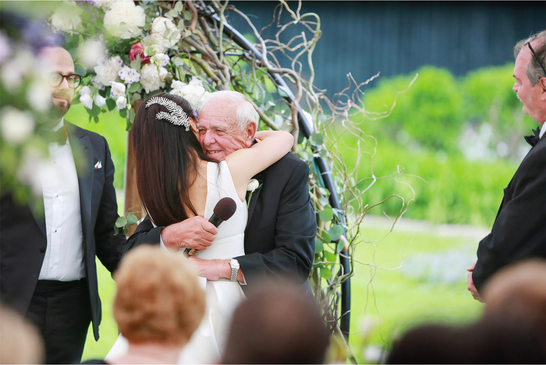 21-Vick-Photography-Wedding-Stouts-Island-Lodge-Wisconsin-Summer-Reception-Outdoor-Toast-Hug-MiJa-and-Lucius.jpg