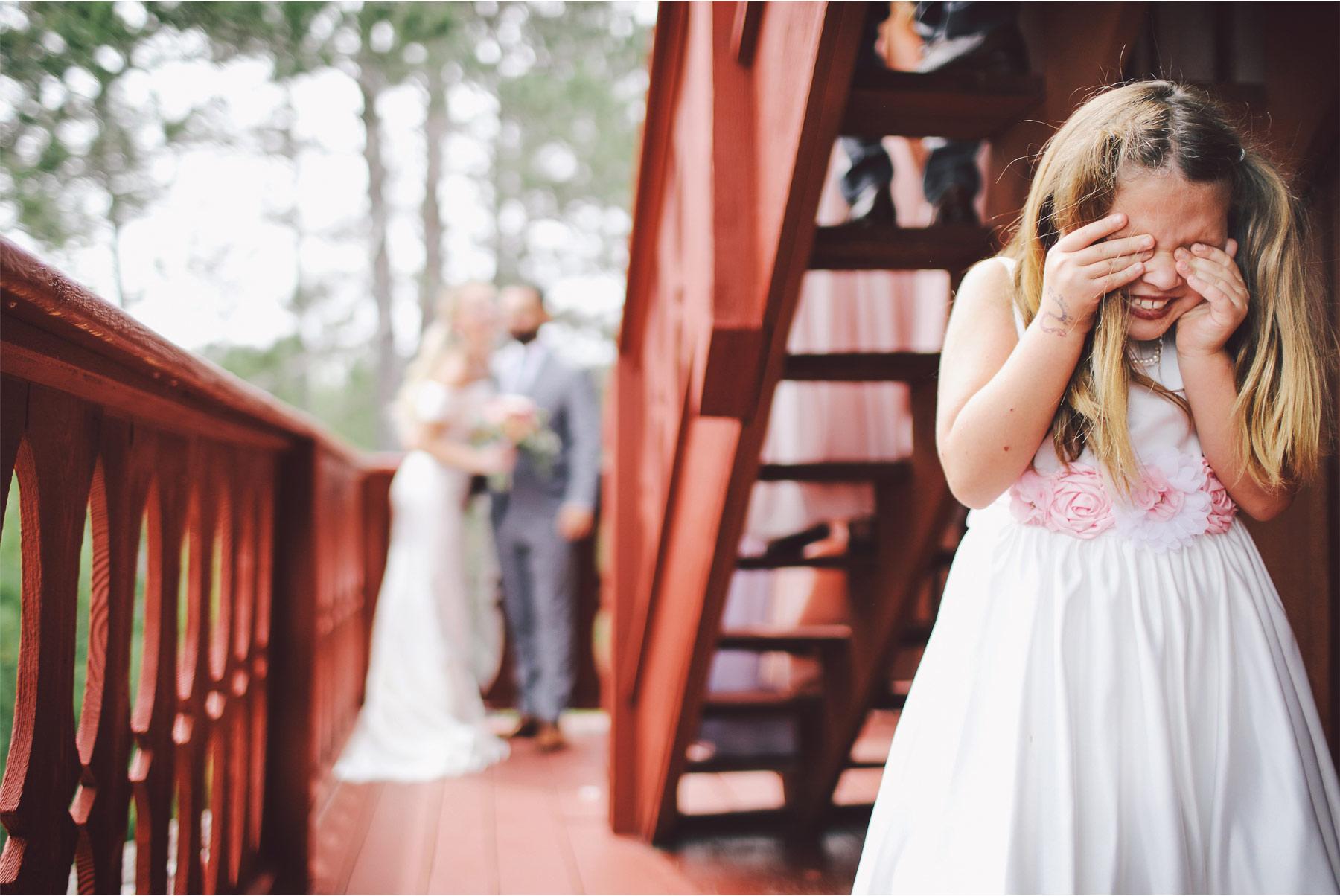 08-Ely-Minnesota-North-Wedding-by-Andrew-Vick-Photography-Bride-Groom-Kiss-Flower-Girl-Cabin-Woods-Katie-and-Joe.jpg