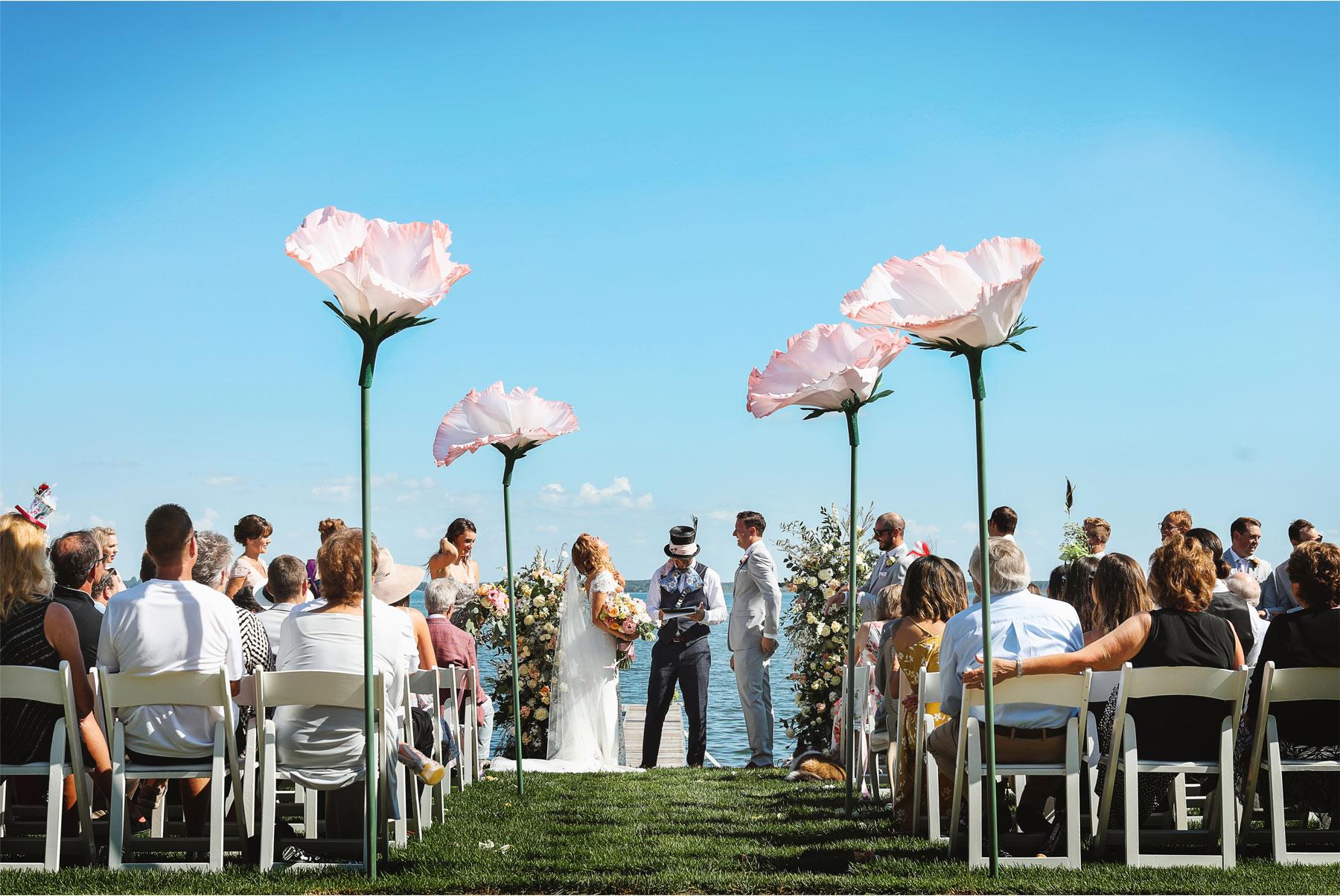 12-Vick-Photography-Wedding-Ottertail-Minnesota-Alice-in-Wonderland-Theme-Ceremony-Outdoor-Giant-Poppys-Bride-Groom-Tess-and-Greg.jpg