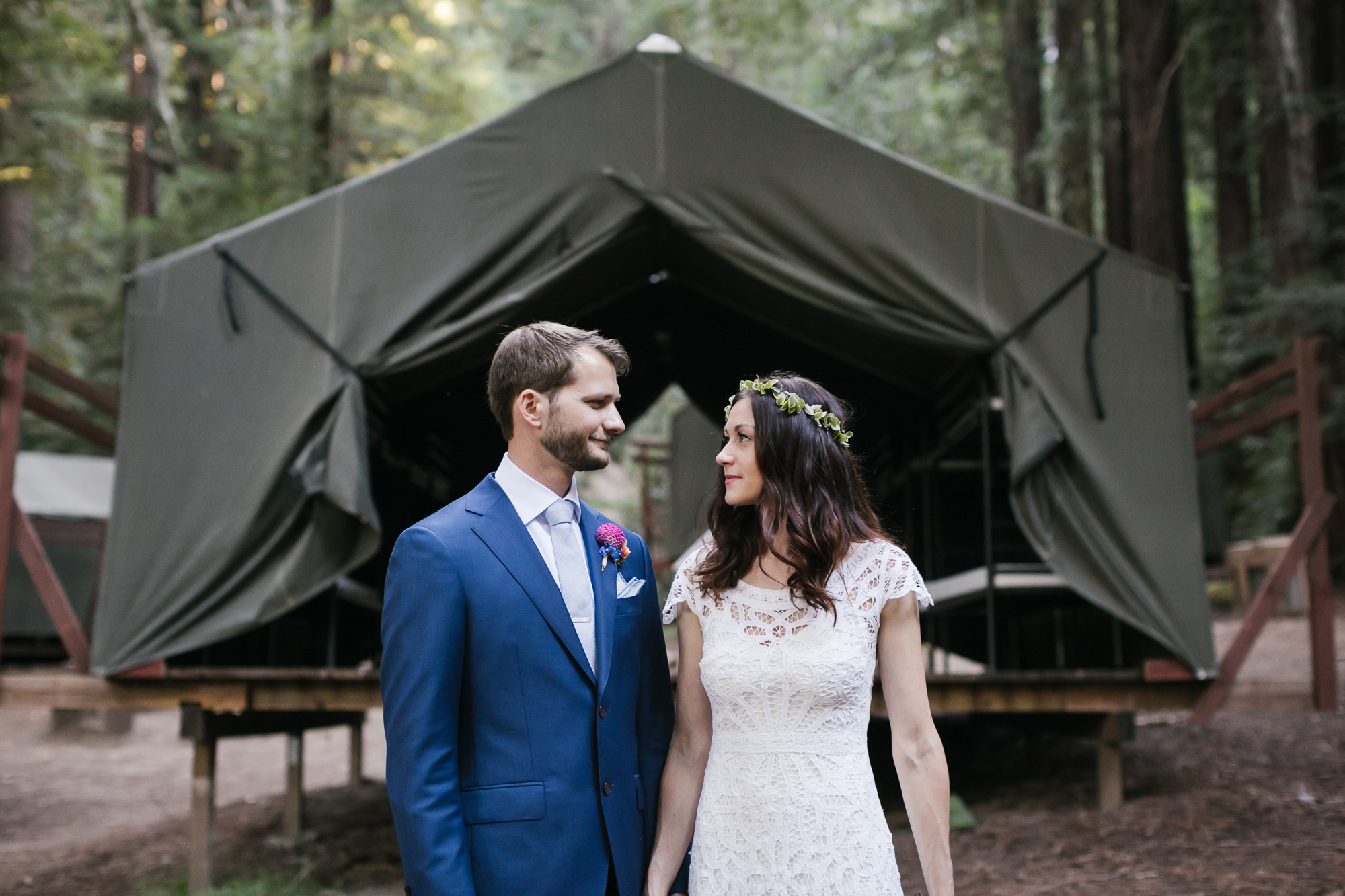 Groom in blue suit and his bride wearing a lace wedding dress and floral crown stand in front of a camp tent in the Santa Cruz Mountains.