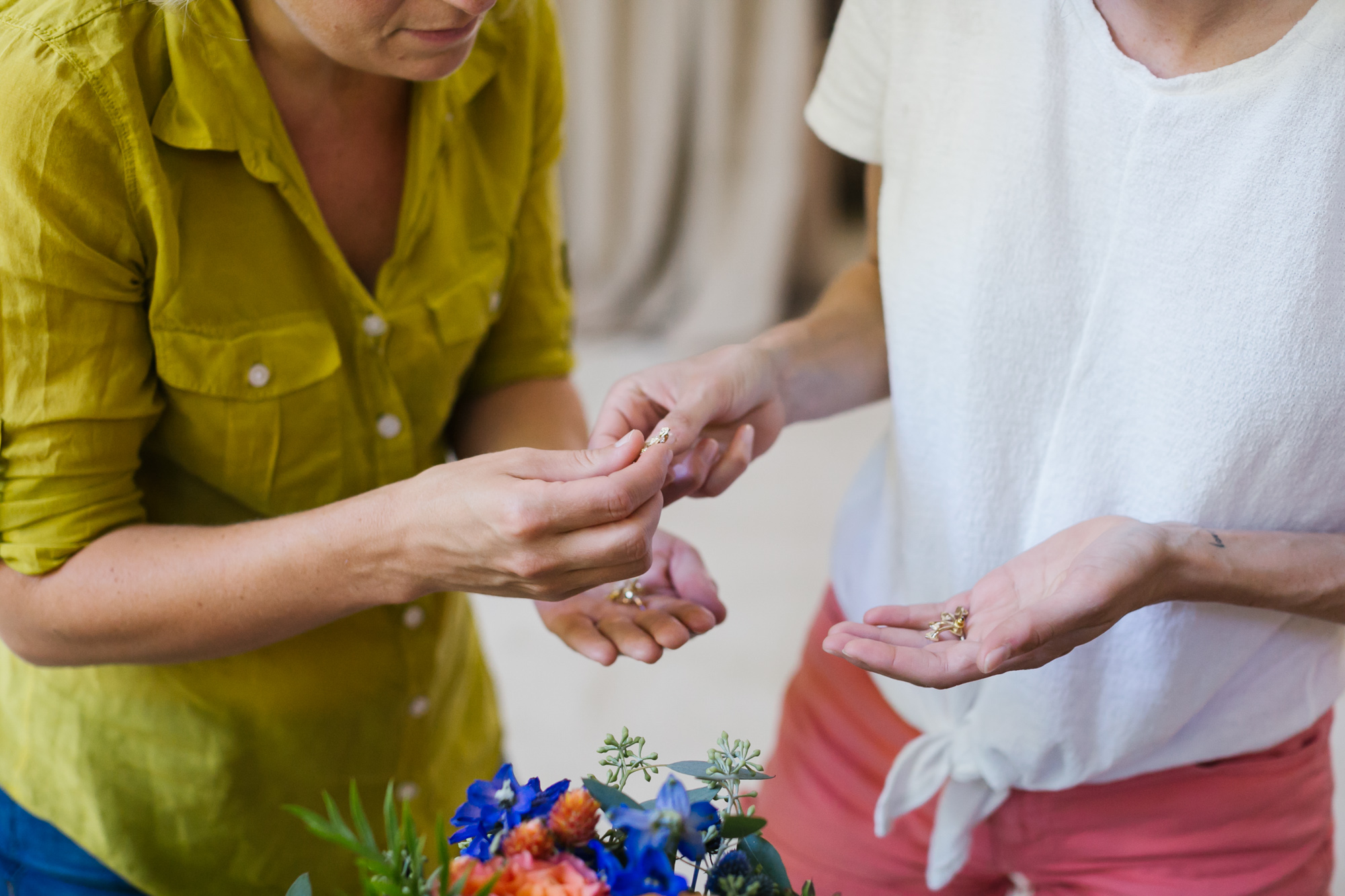 Sister hands bride her wedding jewelry