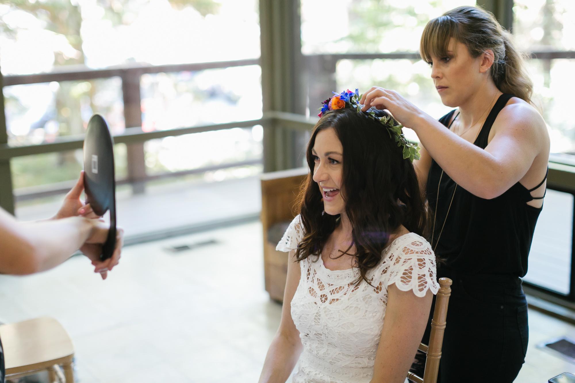 Hairstylist adjust bride's flower crown in front of a mirror