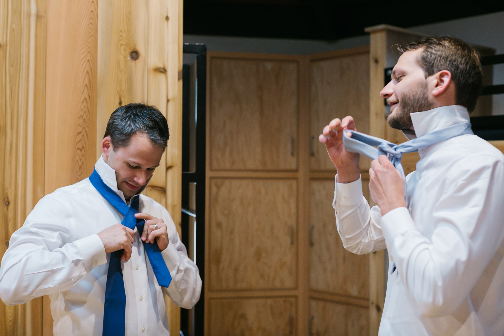 Groom and his brother get dressed, tying ties together in wood cabin