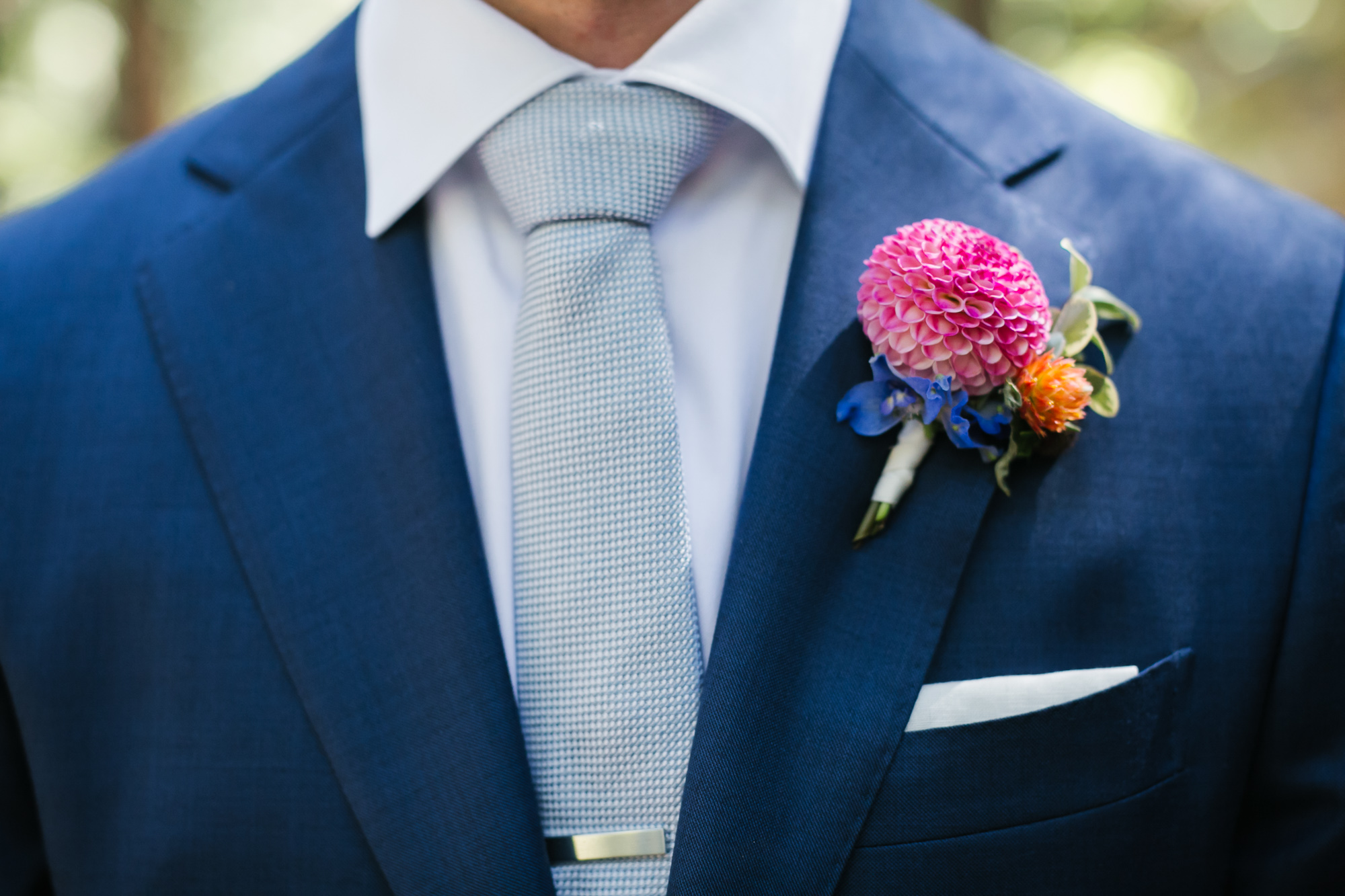 Groom's blue suit with pink dahlia boutonniere