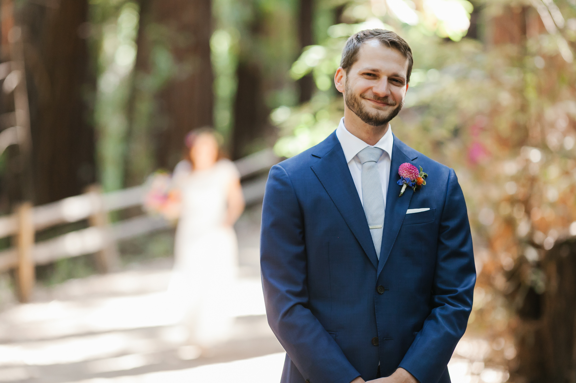 Groom in blue suit smiles as his bride walks up behind him for their first look