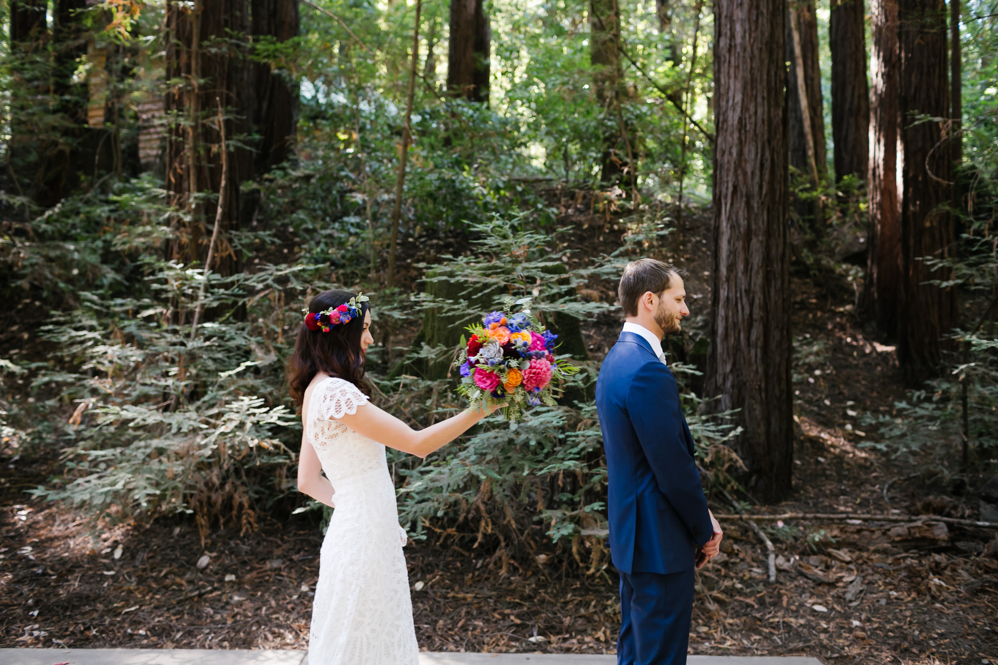 Bride holding colorful bouquet is about to tap her soon to be husband on the shoulder for their first look