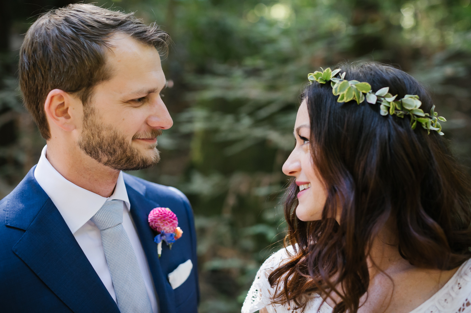 Groom wearing a blue suit smiles at his bride who has a flower crown