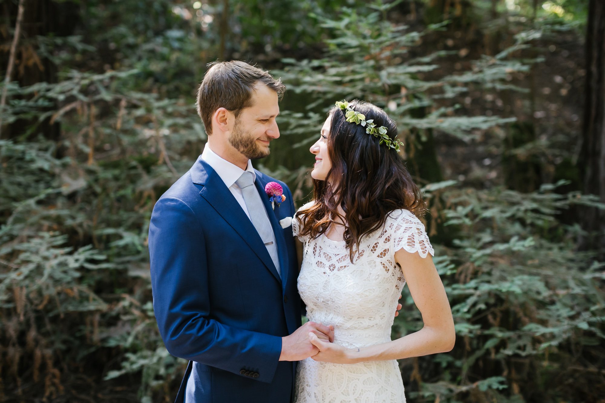 Groom in blue suit holds hands with his bride in a lace dress and flower crown
