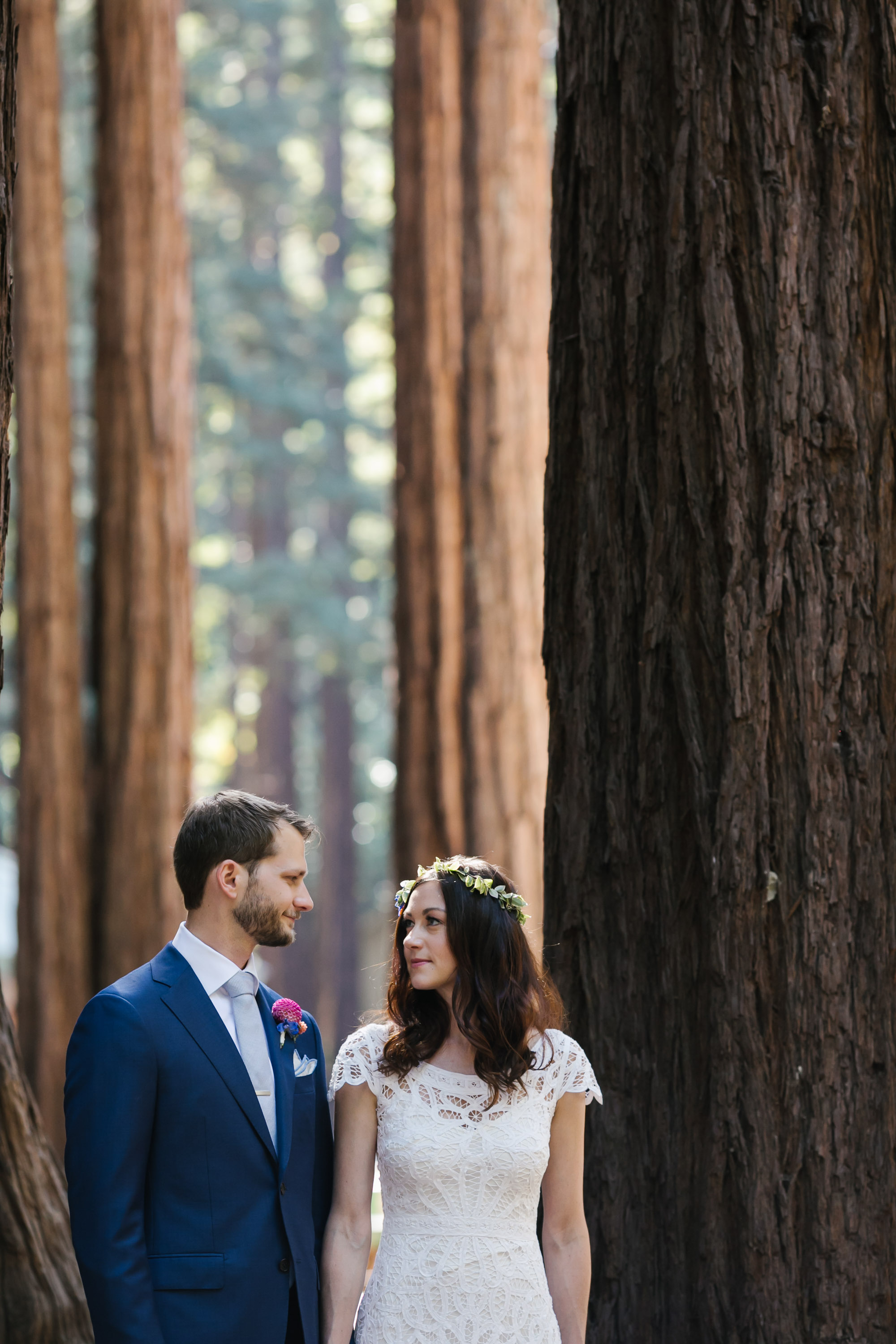 Bride and groom look at each other among massive redwood trees
