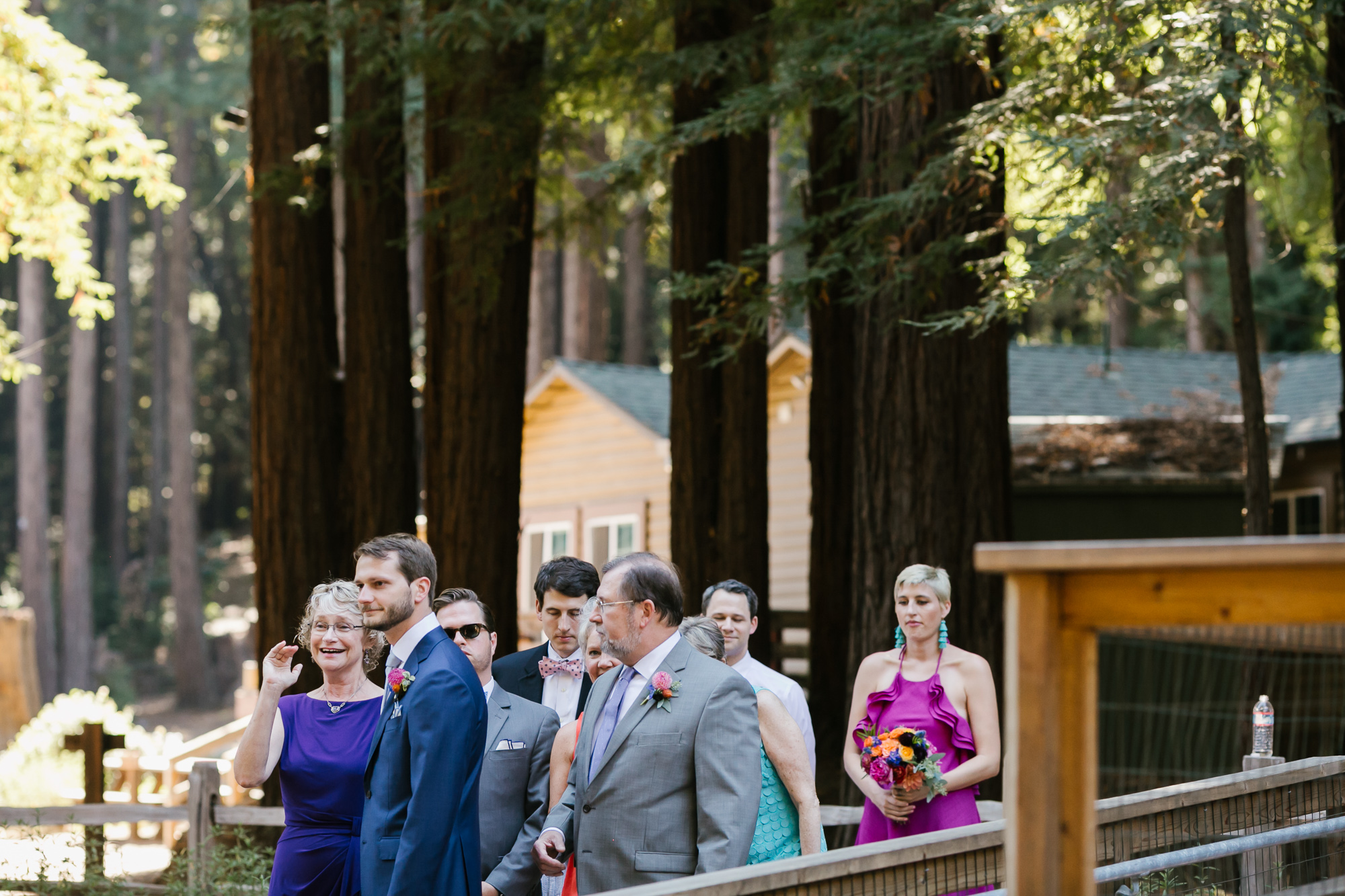 Groom lines up before ceremony with his parents at camp wedding