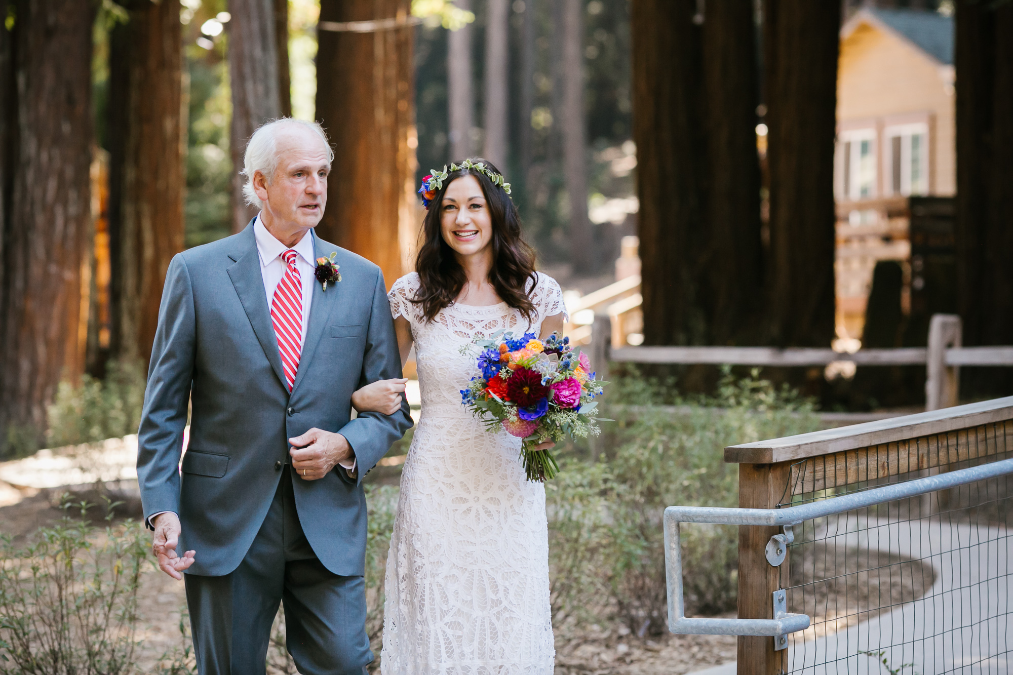 Bride in lace wedding dress and colorful flowers walks arm in arm with her dad
