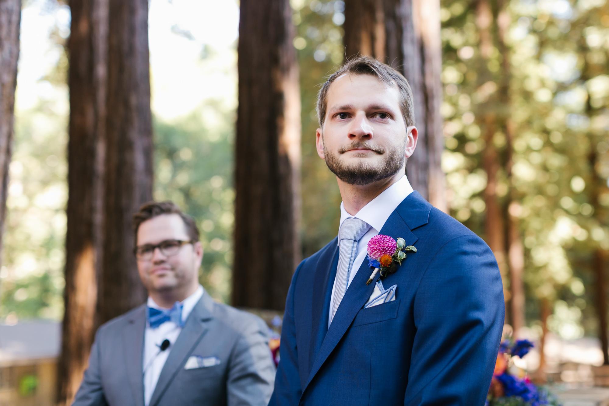Groom in blue suit gets emotional watching his bride walk down the aisle