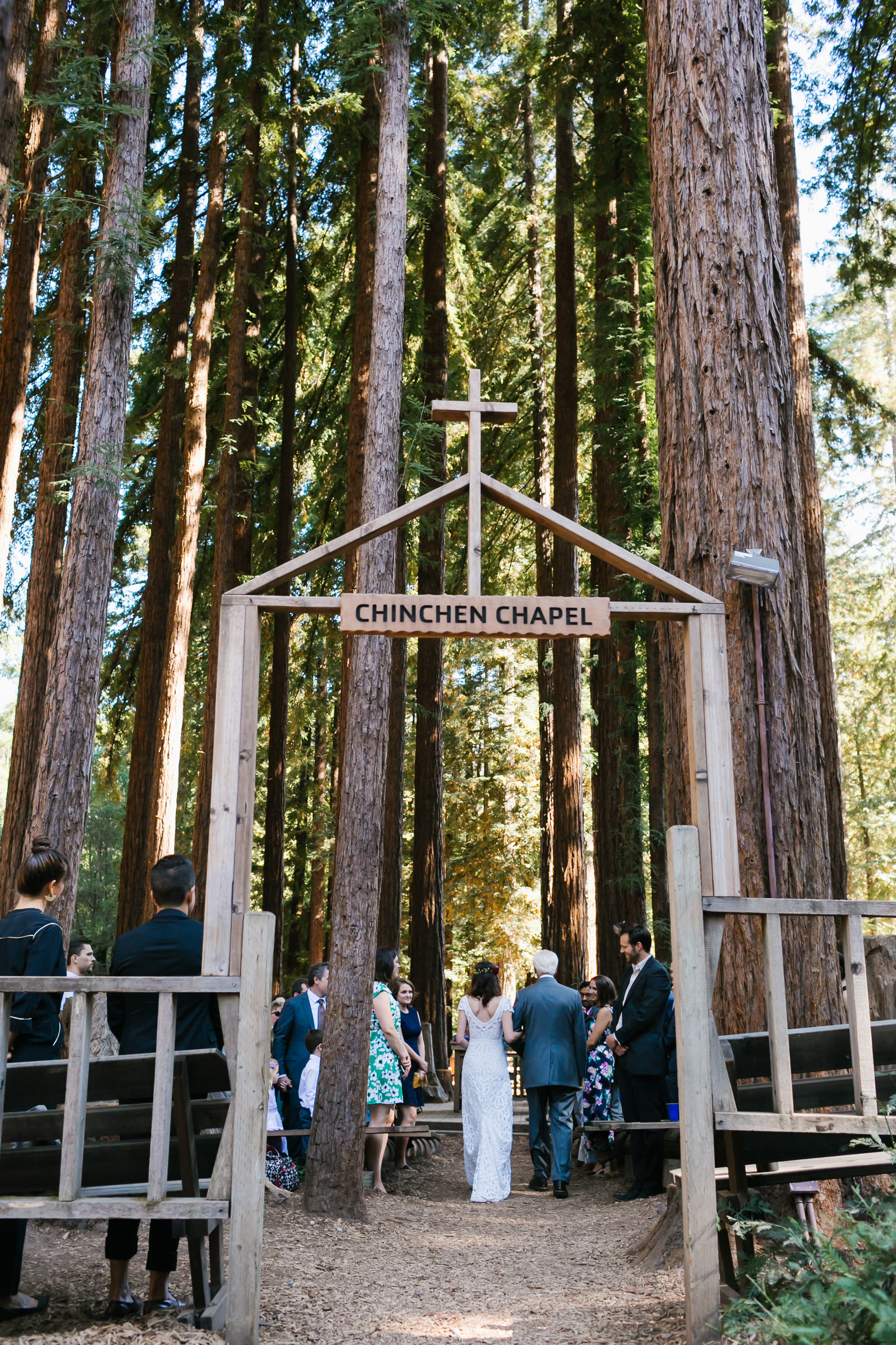 Bride and her father walk into the wedding ceremony in outdoor chapel