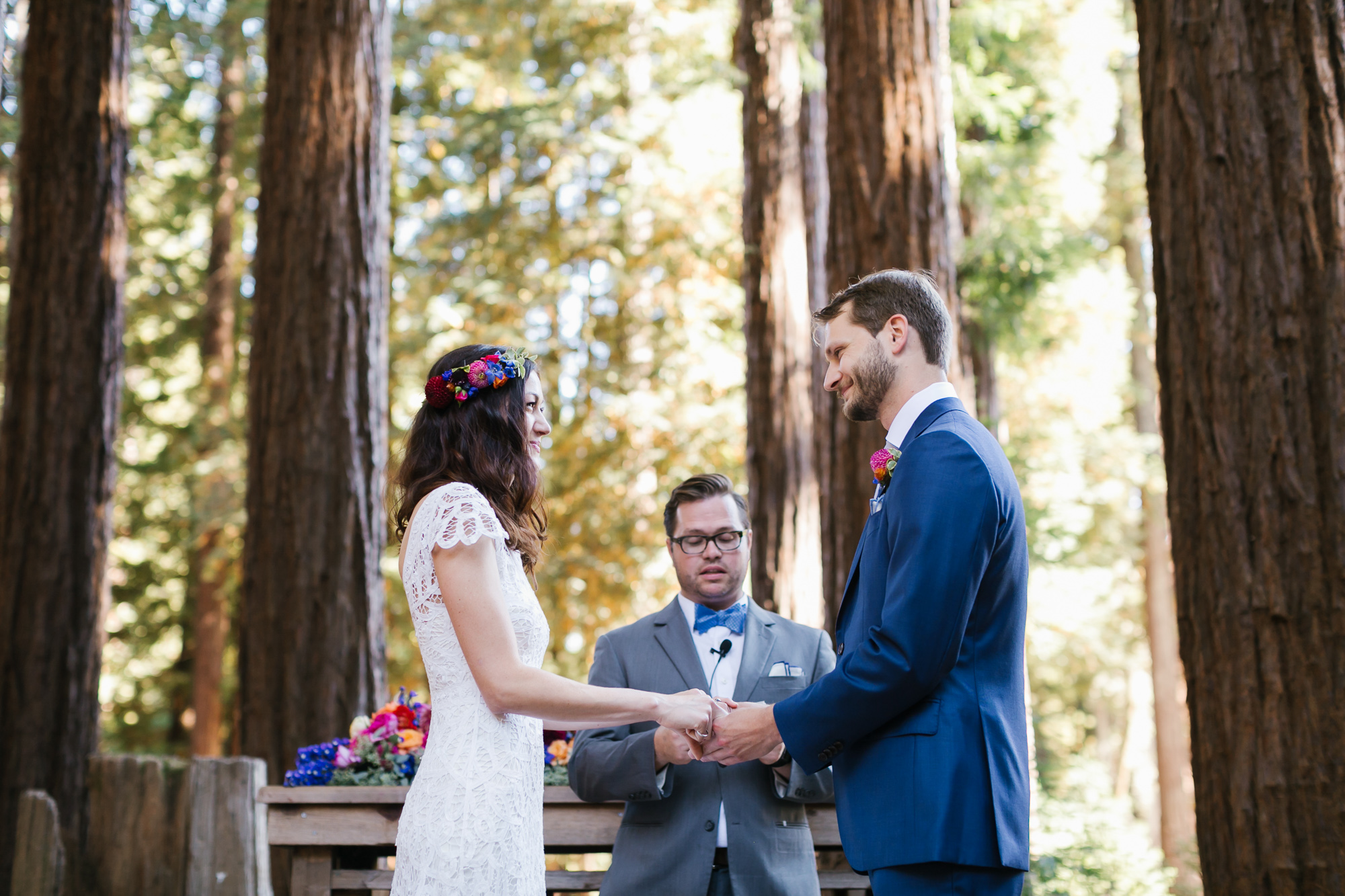 Colorful couple hold hands during their wedding vows outside