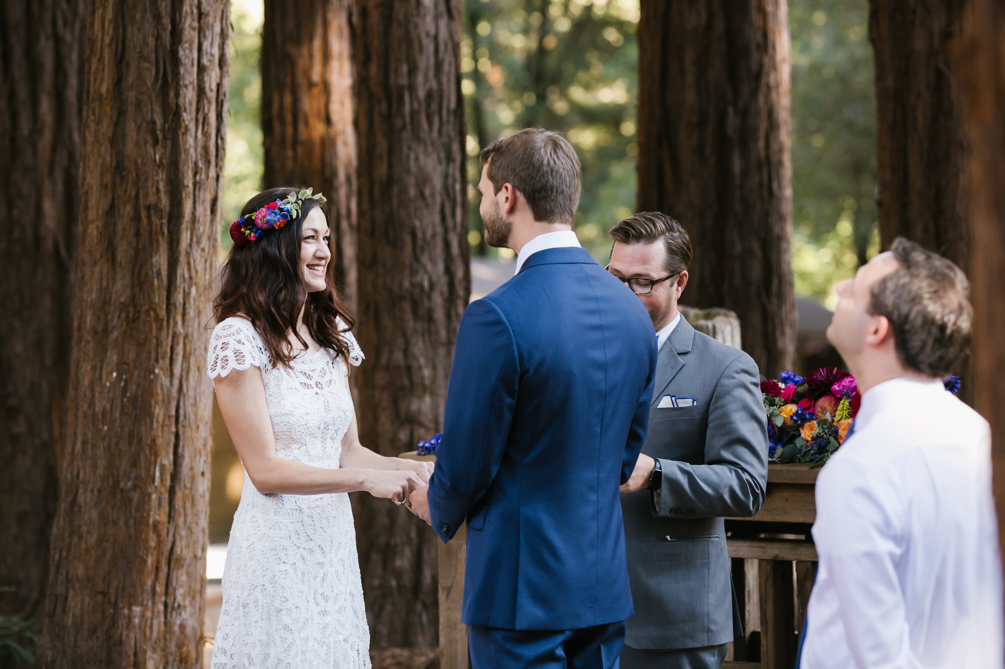 Bride with flower crown smiles at her soon to be husband during their wedding ceremony