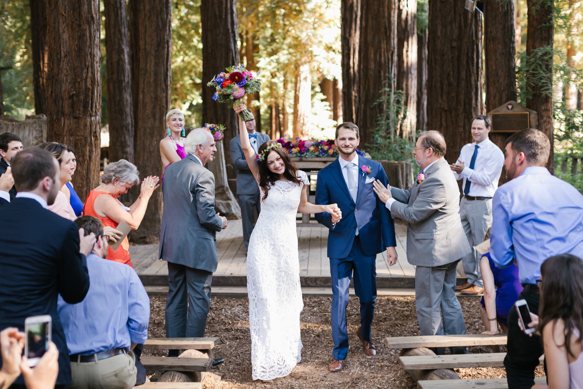 Bride holds her colorful bouquet up over her head in celebration as she walks out of ceremony with her husband