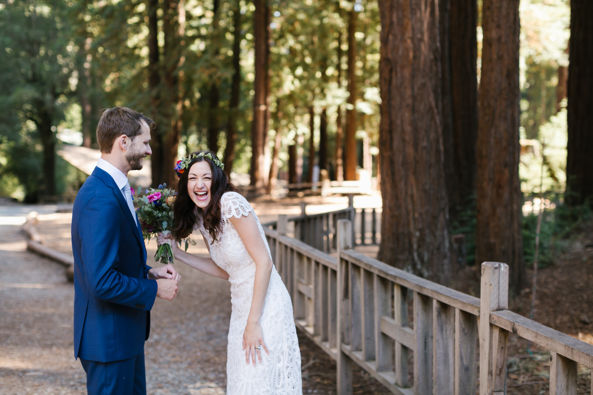 Bride with colorful flowers laughs with joy after her wedding ceremony